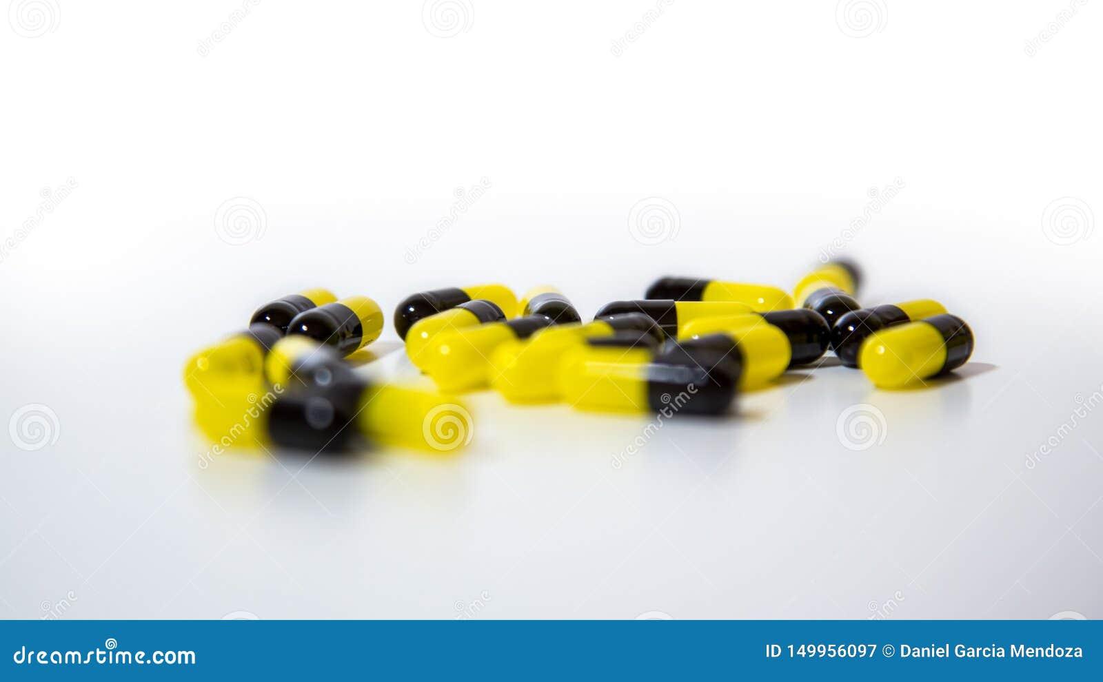 Закройте вверх черных и желтых таблеток и медицины планшетов на белой предпосылке