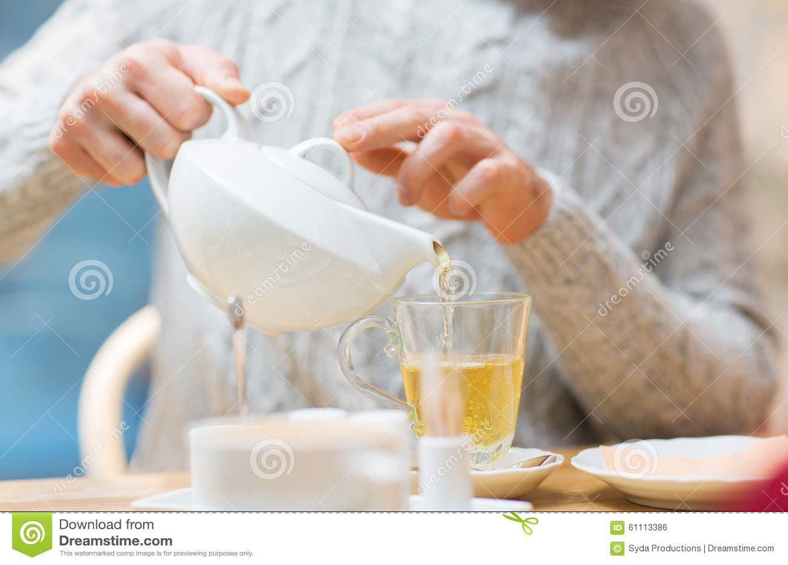 Закройте вверх человека с чаем бака лить на кафе