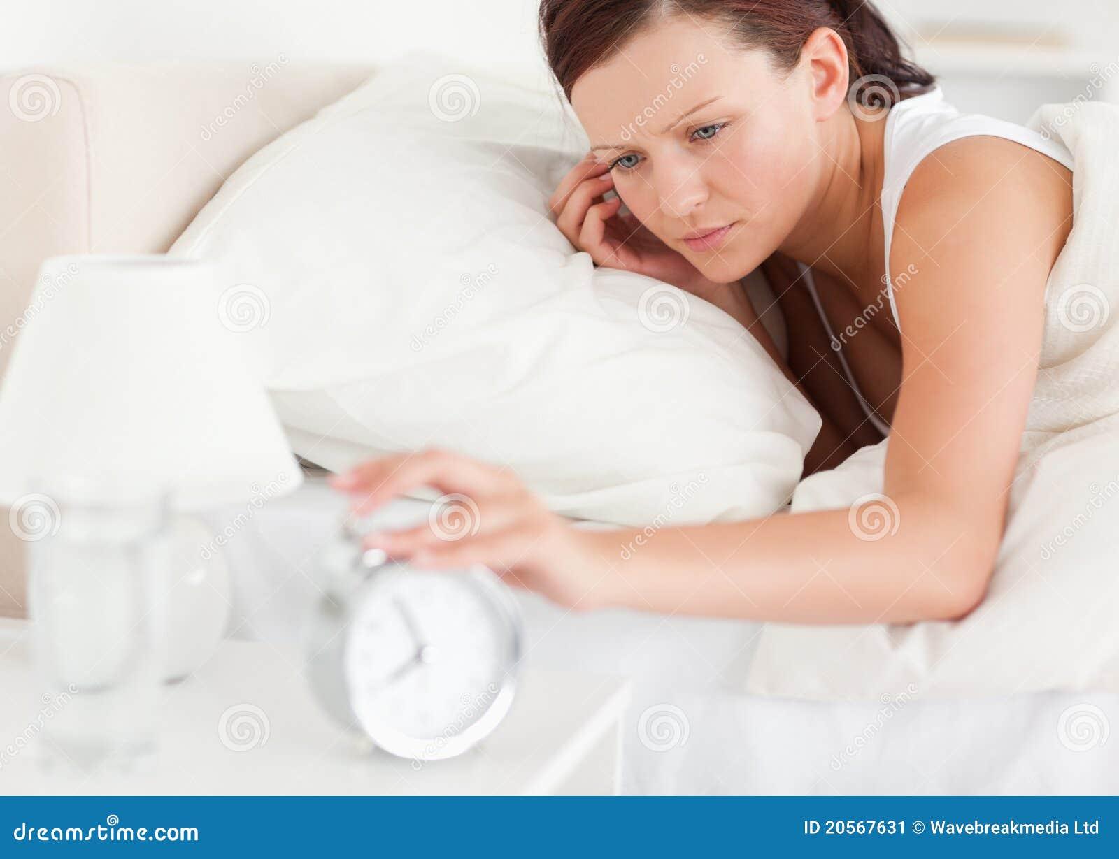 Закройте вверх Red-haired женщины лежа в кровати