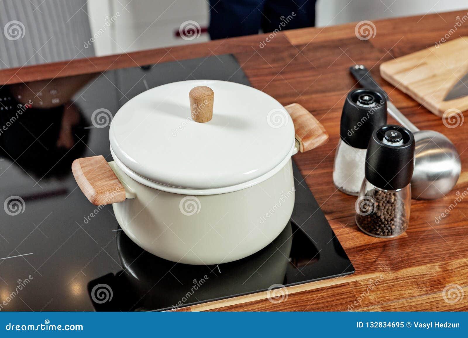 Закрытая белая кастрюлька с деревянными ручками на черной плите и стеклянными мельницами специи с papper и соль на деревянной таб