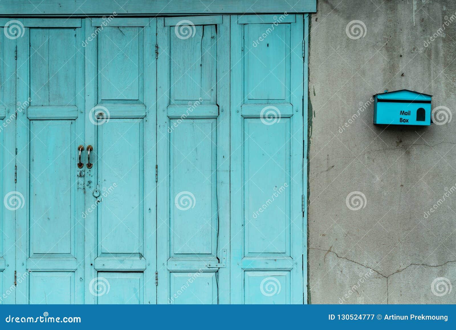 Закрытая зеленая или голубая деревянная дверь и пустой почтовый ящик на треснутой бетонной стене дома Старый дом с треснутой стен