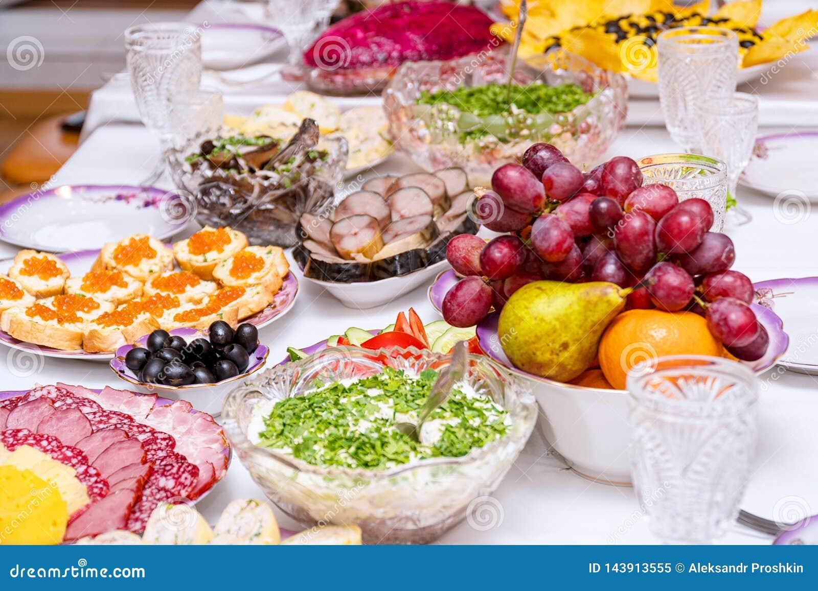 Закуски, плоды, сэндвичи, салаты, икра и отрезать на таблице праздника