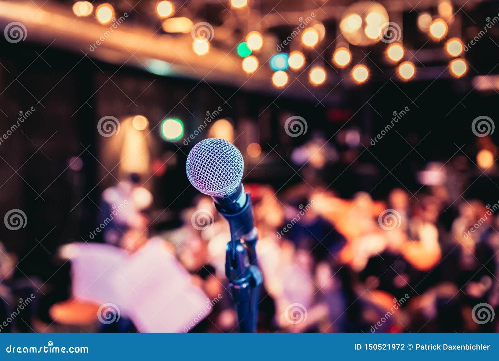 Зала события: Закройте вверх стойки микрофона, мест с аудиторией в расплывчатой предпосылке