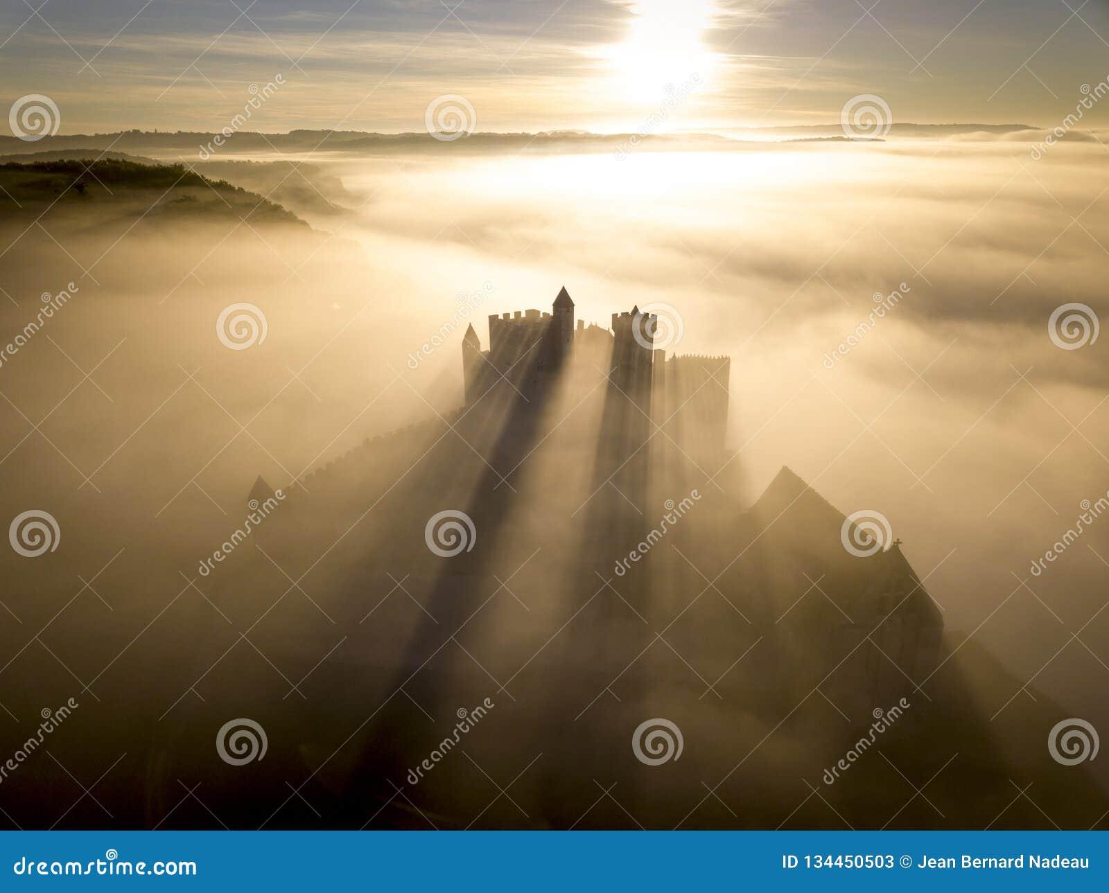 Замок Beynac в тумане в раннем утре Perigord Noir Дордоне Франции