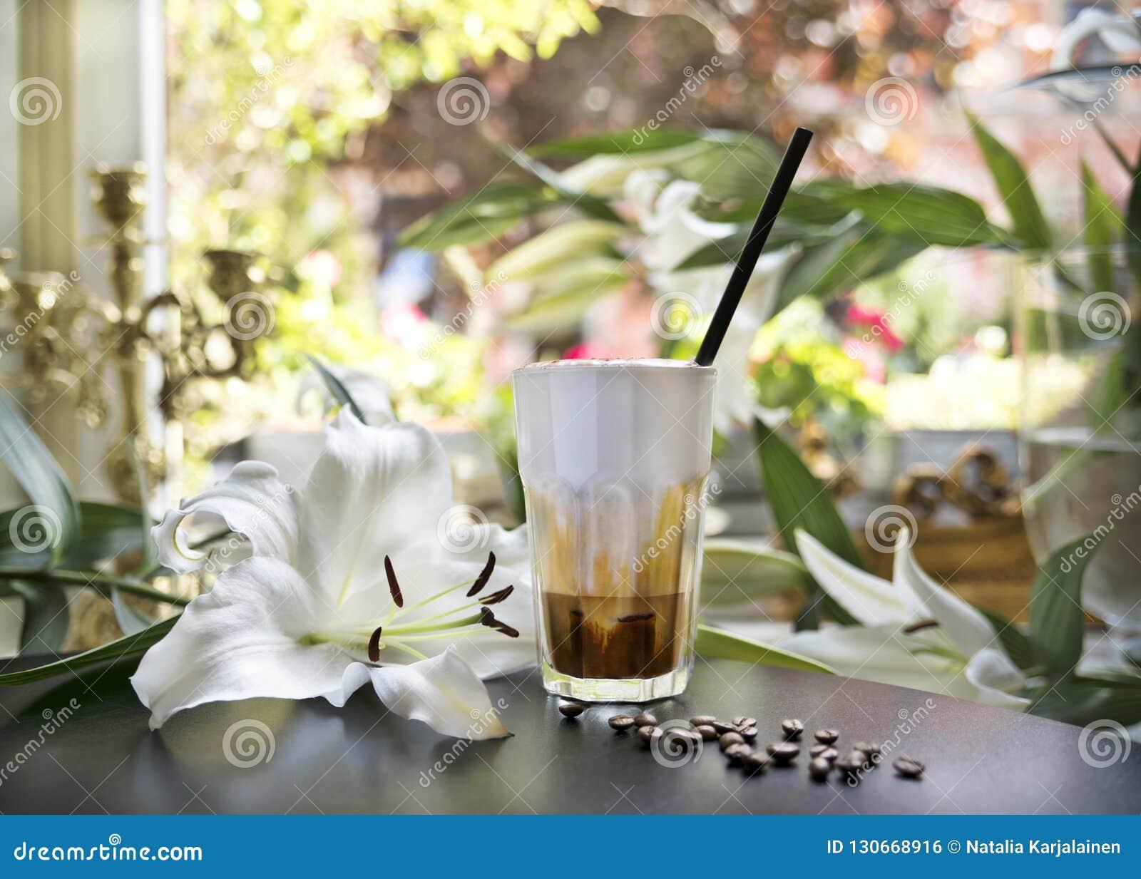 Замороженное стекло кофе latte на таблице в ретро ресторане и café на фоне окна и белых лилий