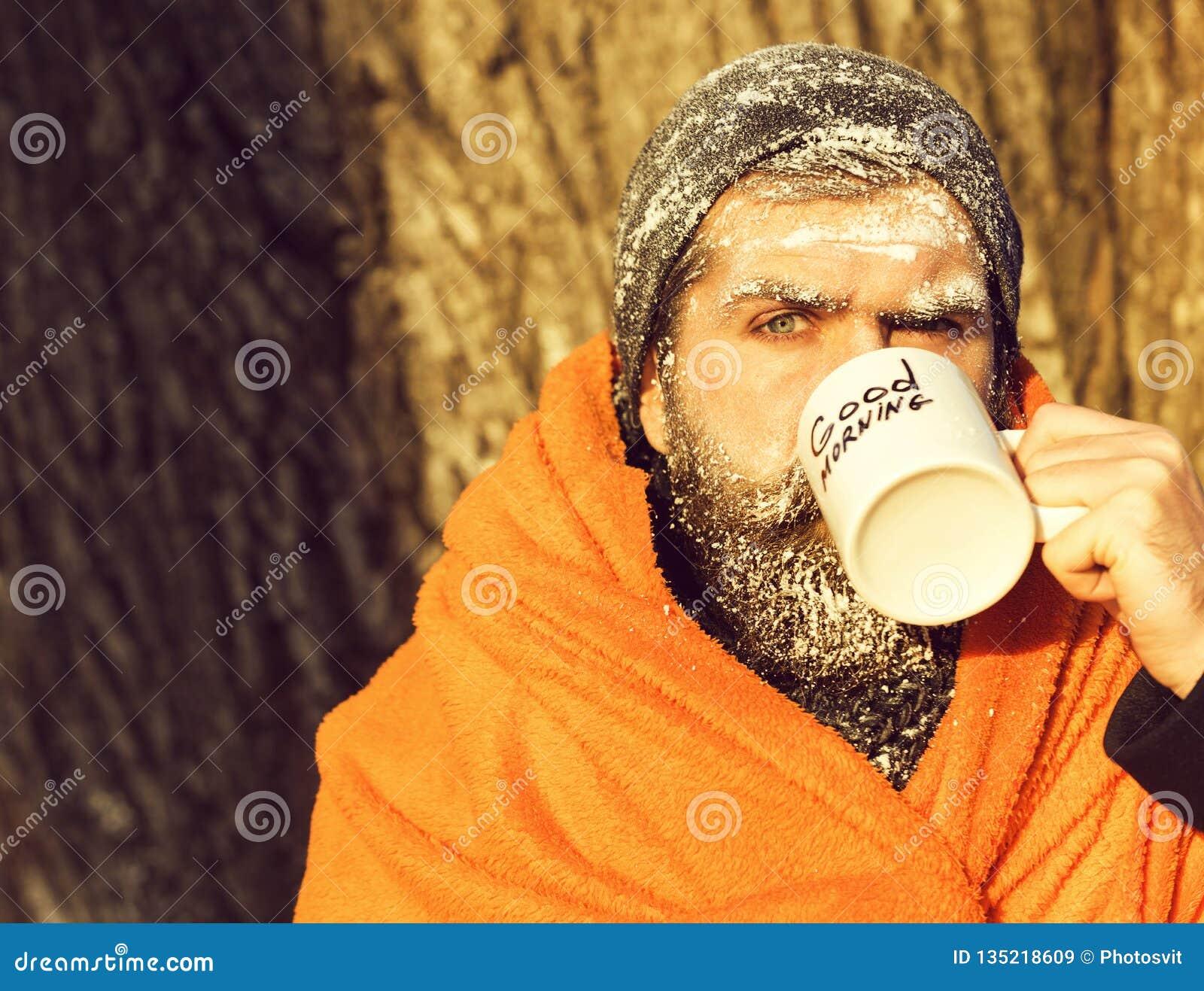 Замороженный человек, бородатый битник, при борода и усик предусматриванные с белым заморозком обернутые в оранжевом одеяле с гре