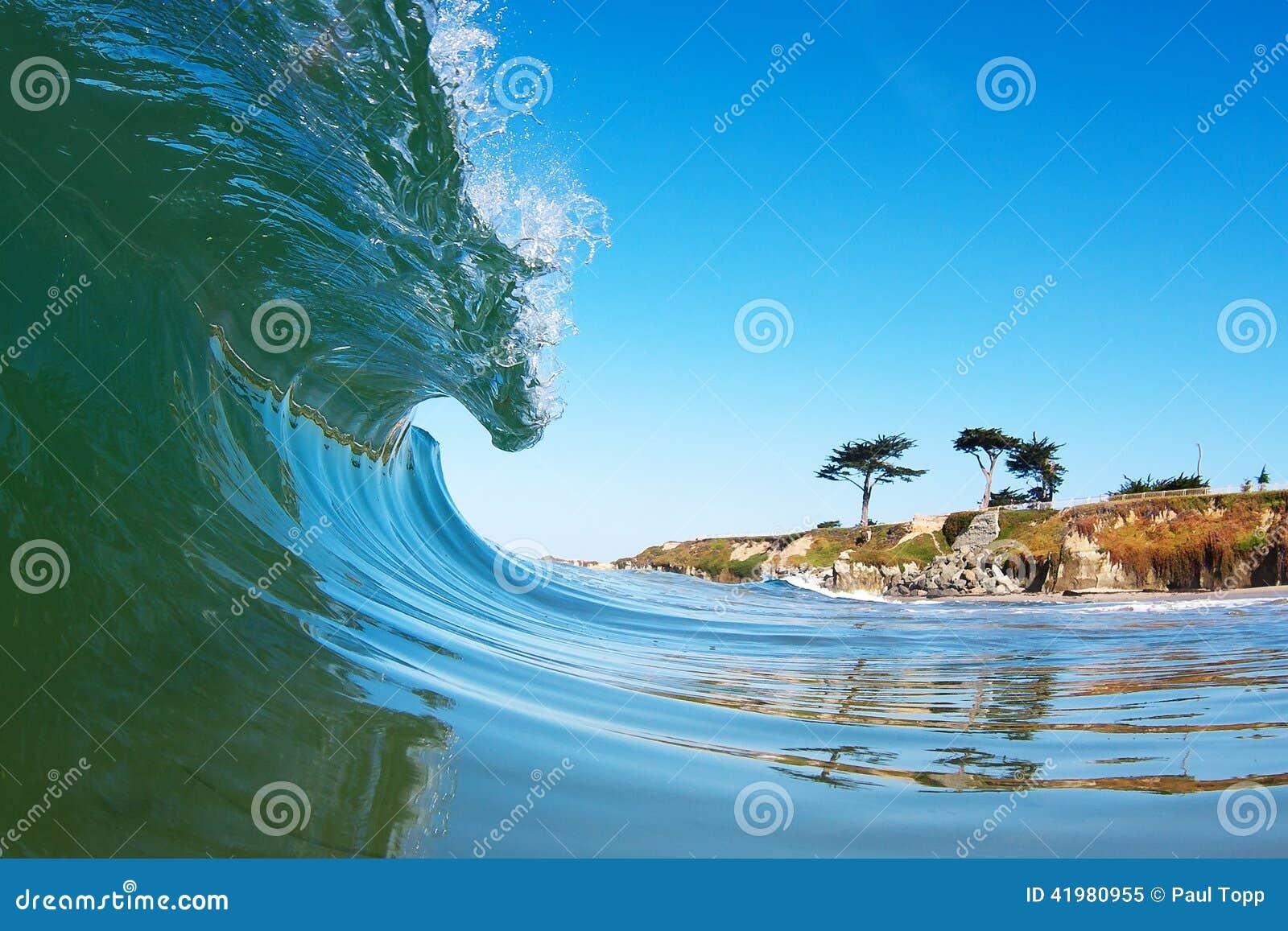 Занимаясь серфингом волна ломая около берега в Калифорнии