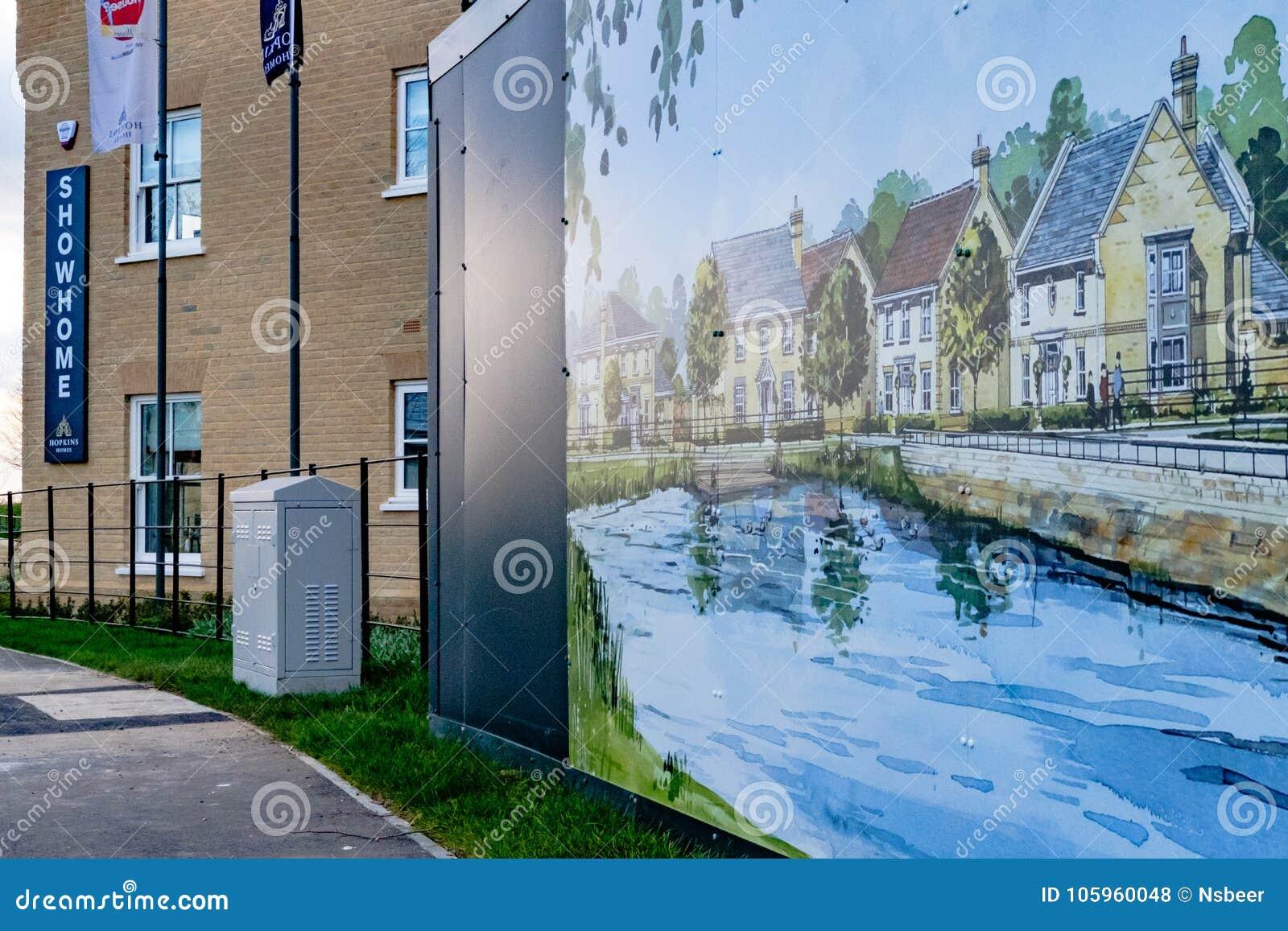 Заново построенные дома и знамя выставки увиденные перед большим, рекламирующ барьер