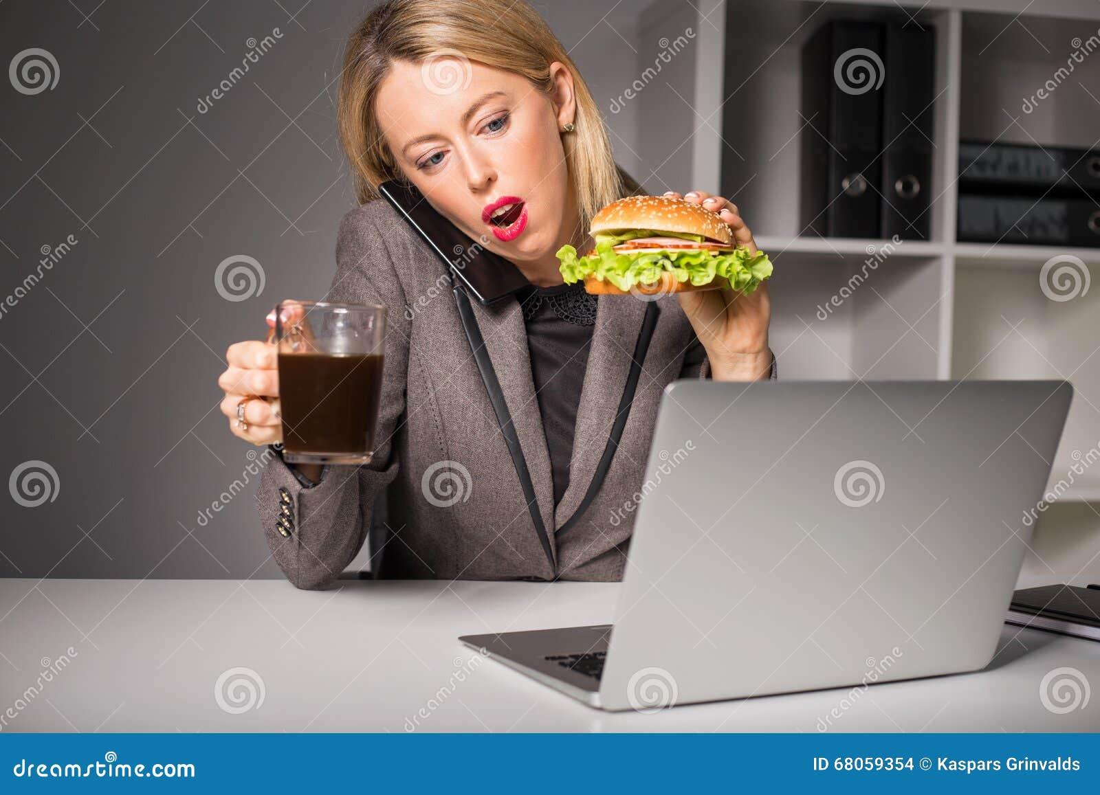 Занятая женщина говоря на телефоне пока имеющ бургер и кофе