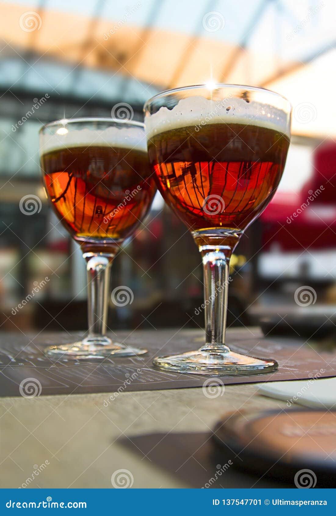 Запачкайте светлую предпосылку с 2 стеклами темного пива на таблице кафа