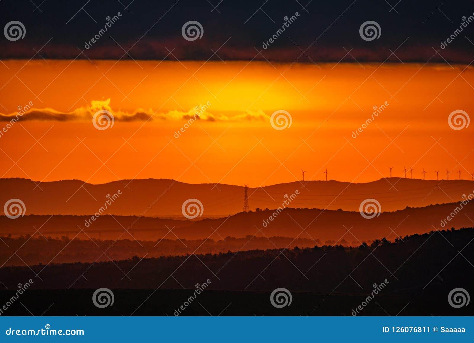 Запачканный восход солнца с оранжевыми цветами и слоями горы