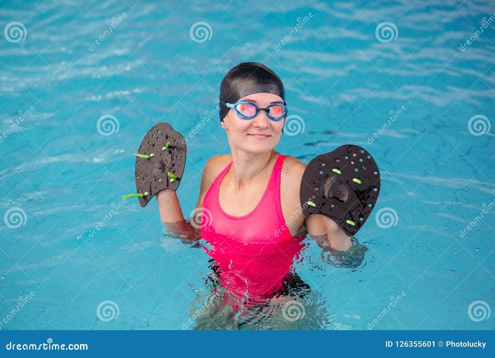 Заплывание маленькой девочки в водном бассейне с специальным оборудованием для руки