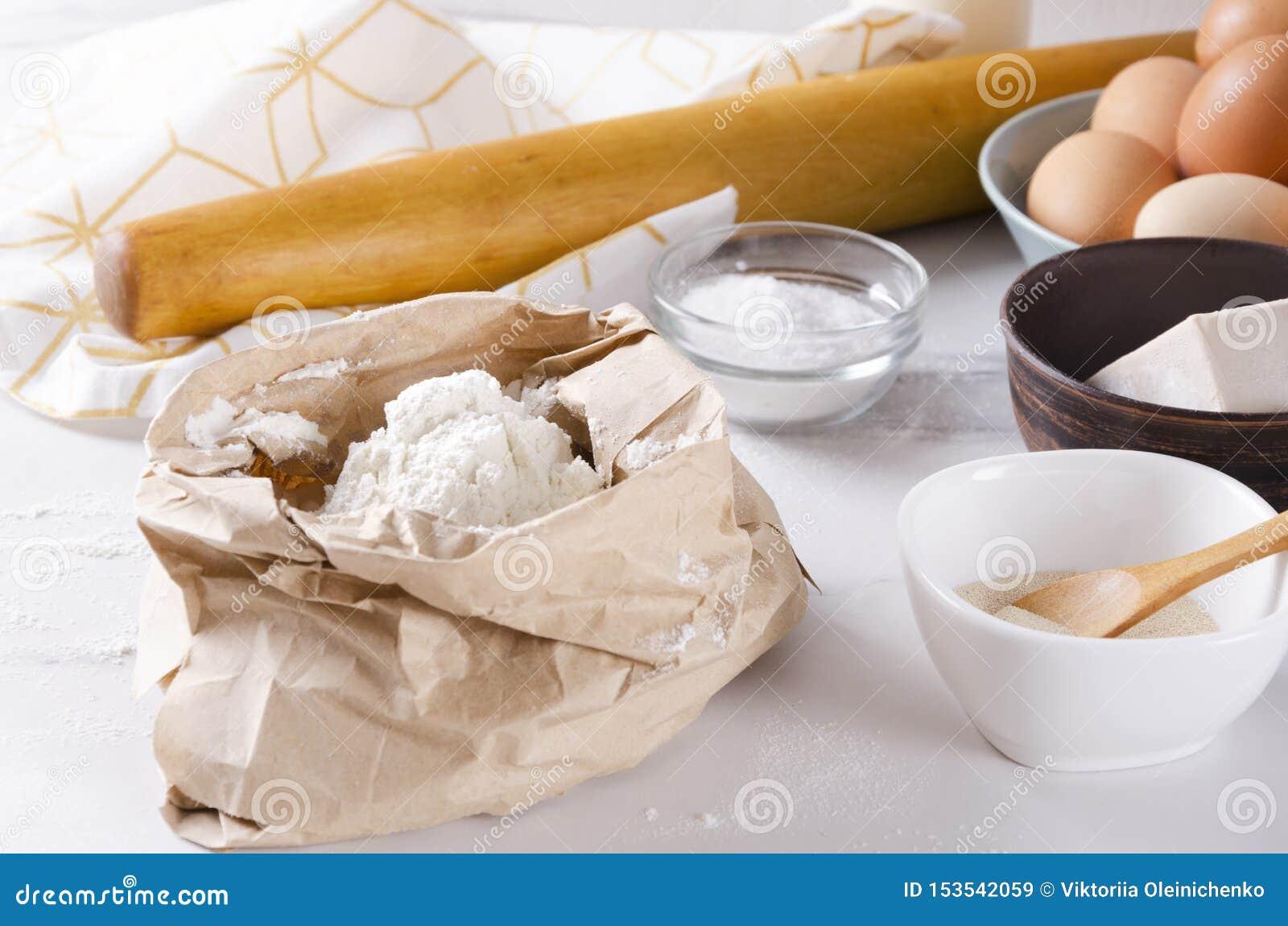 Заполнение бумажного мешка муки, яя, соли, дрожжей, вращающей оси, полотенца кухни на белой таблице Процесс подготовки теста