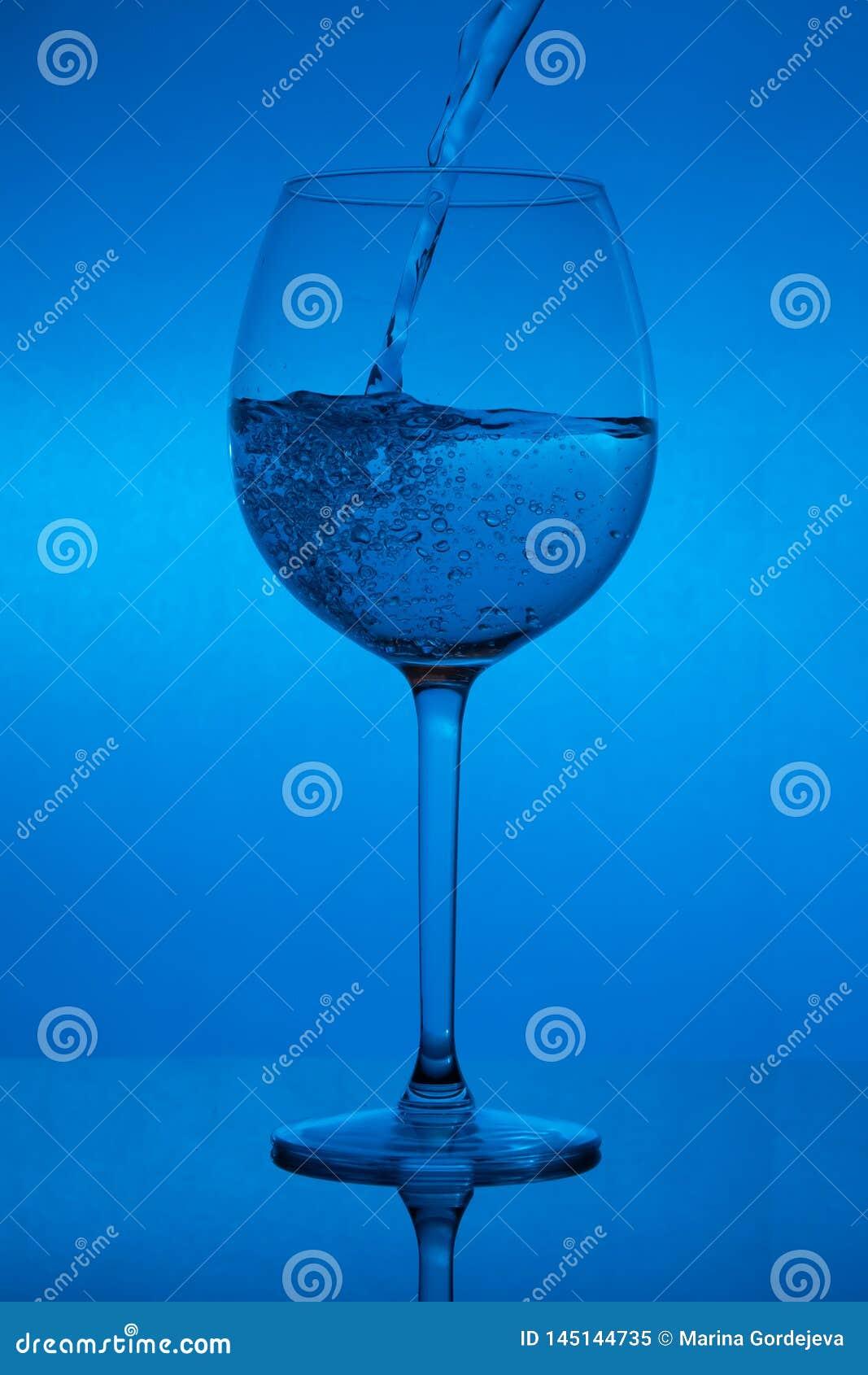 Заполнять стекло, лить рюмка на голубой предпосылке