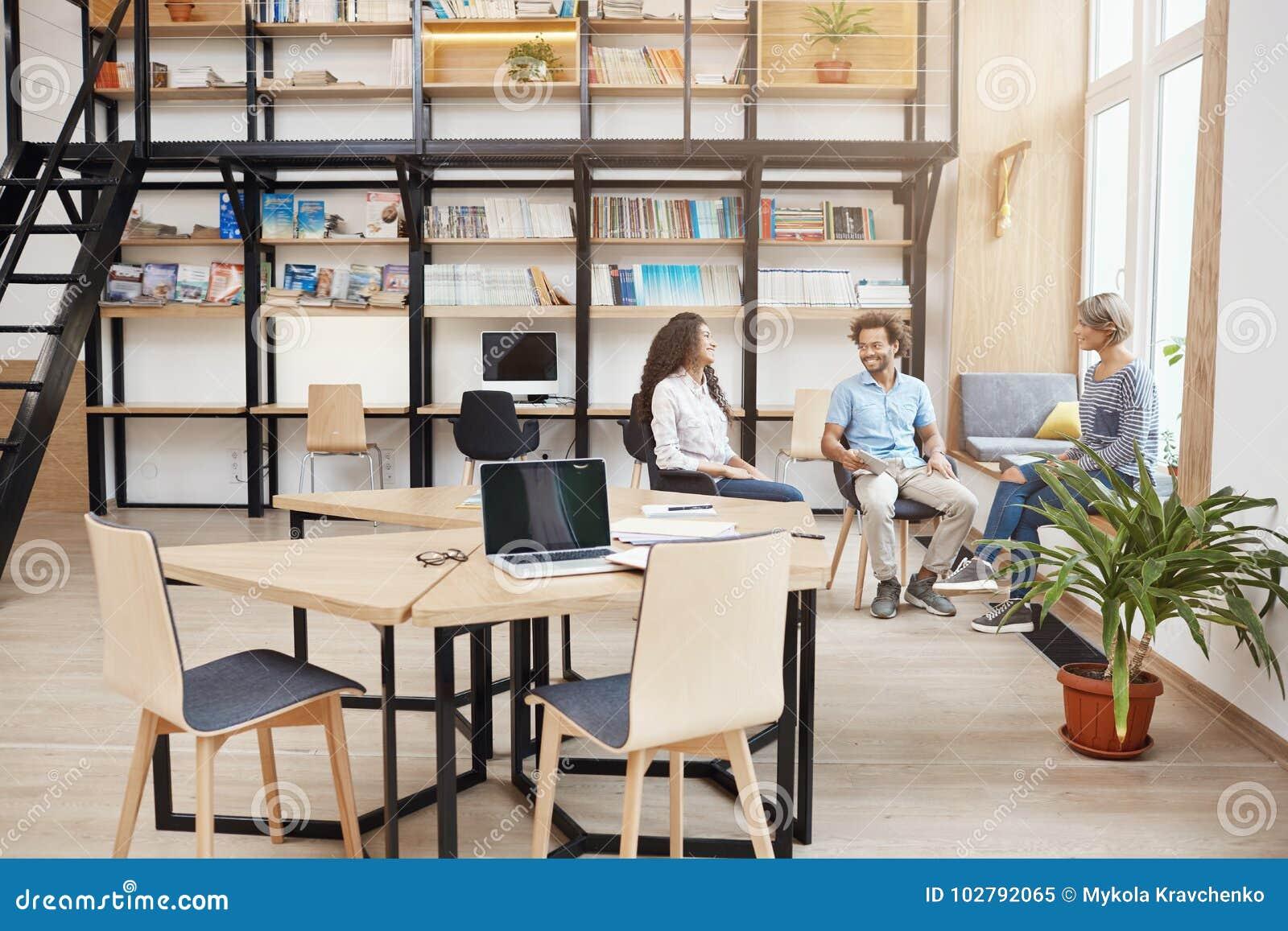 Запуск, дело, концепция сыгранности Группа в составе молодые люди перспективы на встрече в большой современной библиотеке говоря