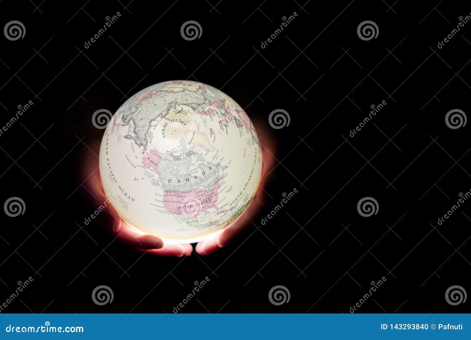 Зарево глобуса в руках коричневейте покрытую землю дня относящое к окружающей среде листво идет идя зеленый вал текста лозунгов в