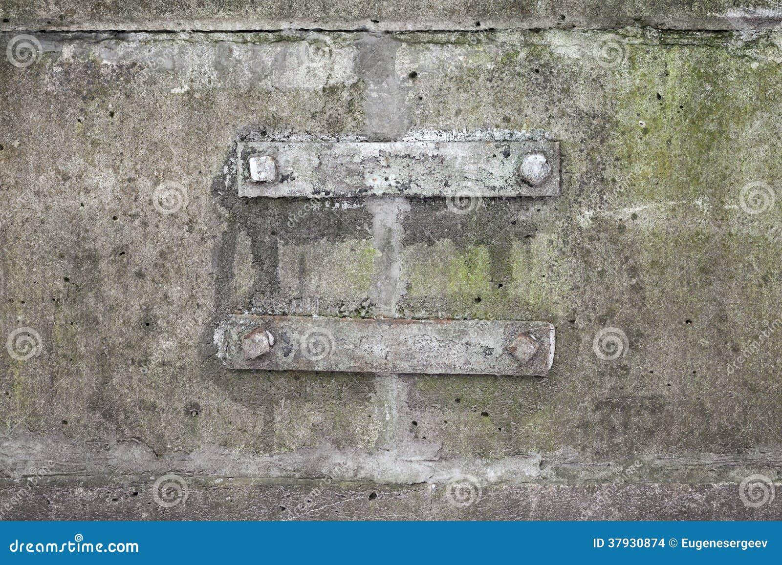 Заржаветые детали кронштейна стальные на бетонной стене
