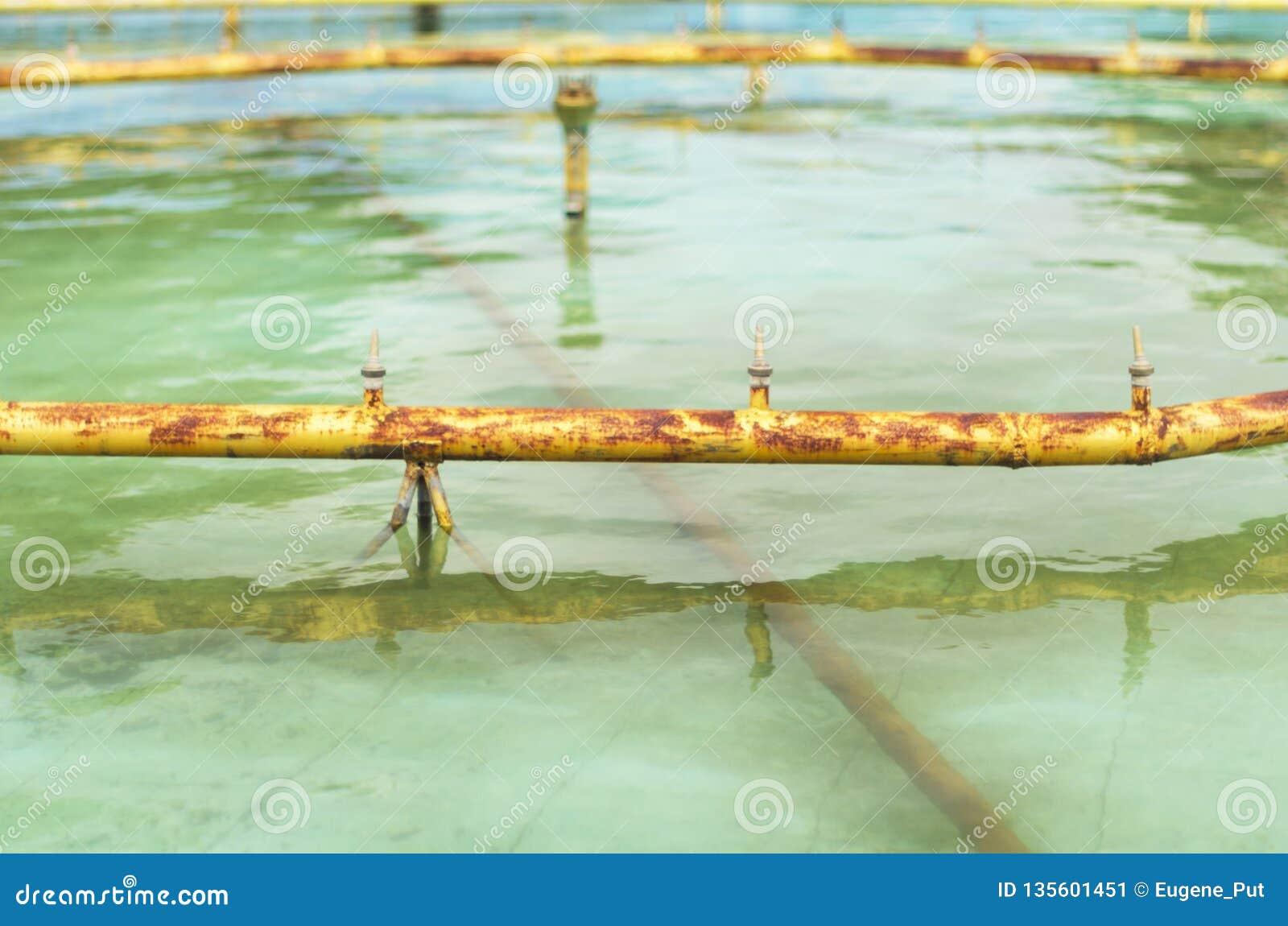 Заржаветые желтые трубы и струи воды фонтана, который стекли для обслуживания или обслуживать на летний день