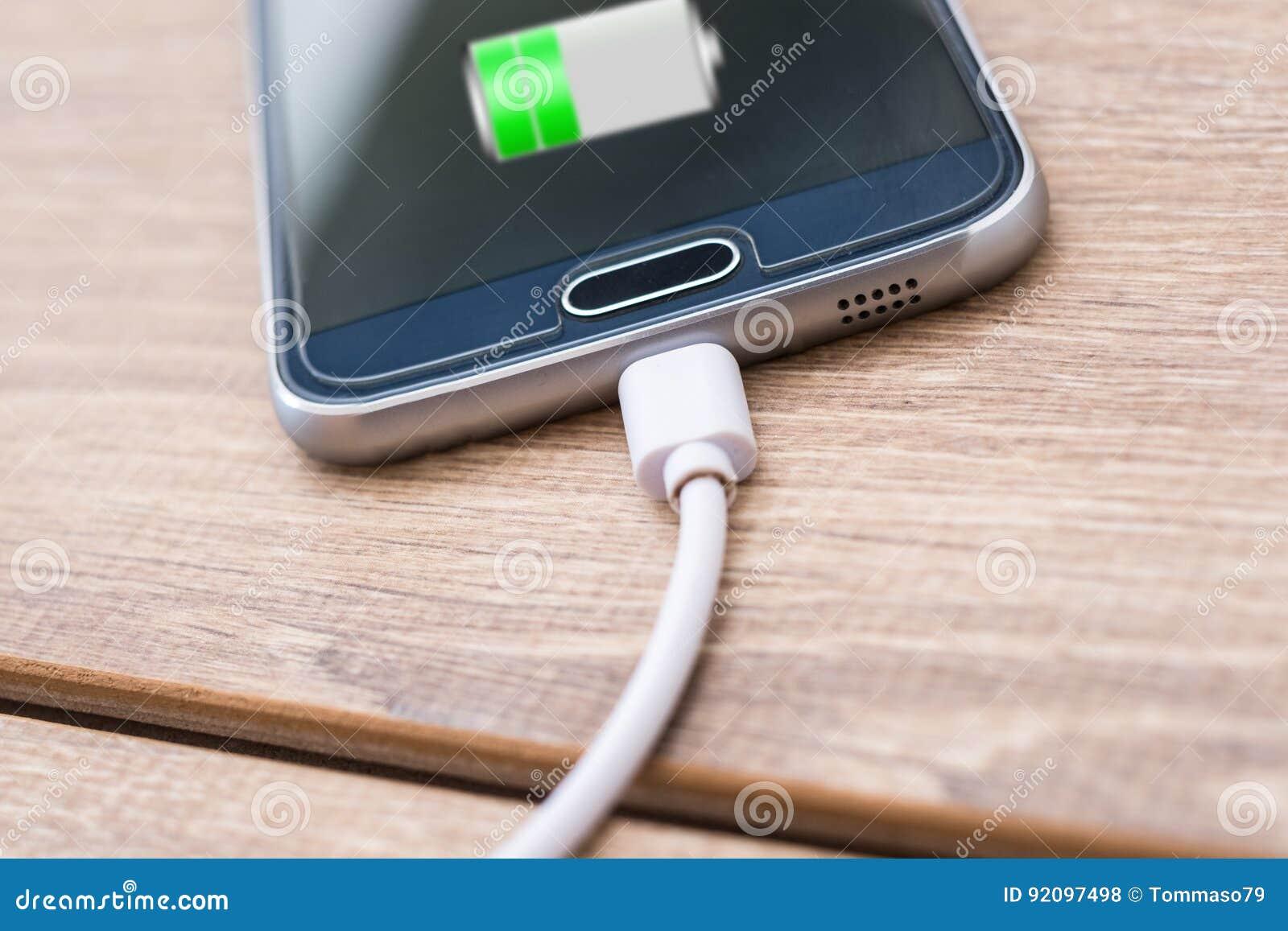 Заряжатель мобильного телефона и батареи привязывает на столе офиса