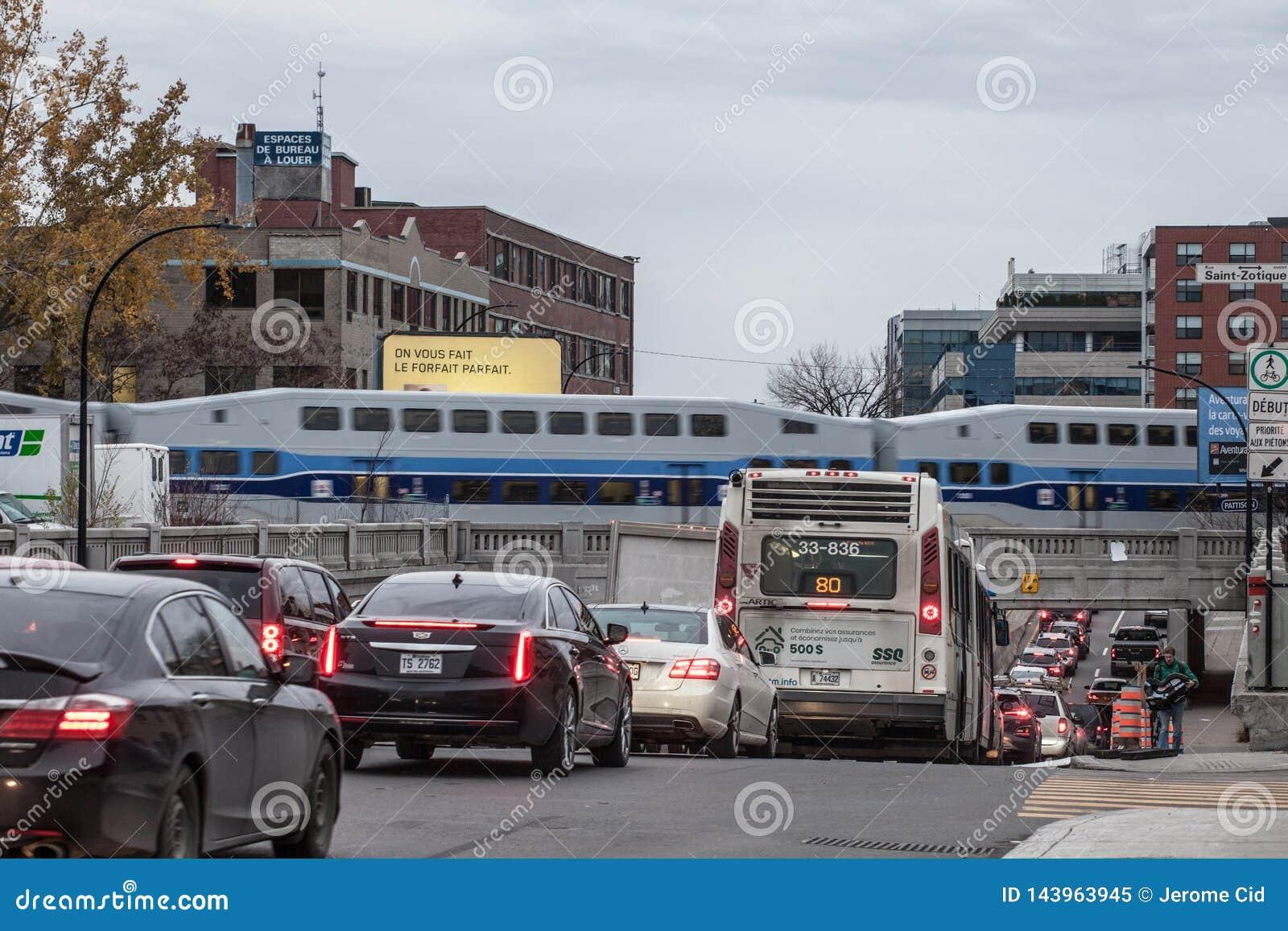Затор движения на бульваре St Laurent с автомобилями и автобусом пока пригородный поезд Allo Exo Монреаля
