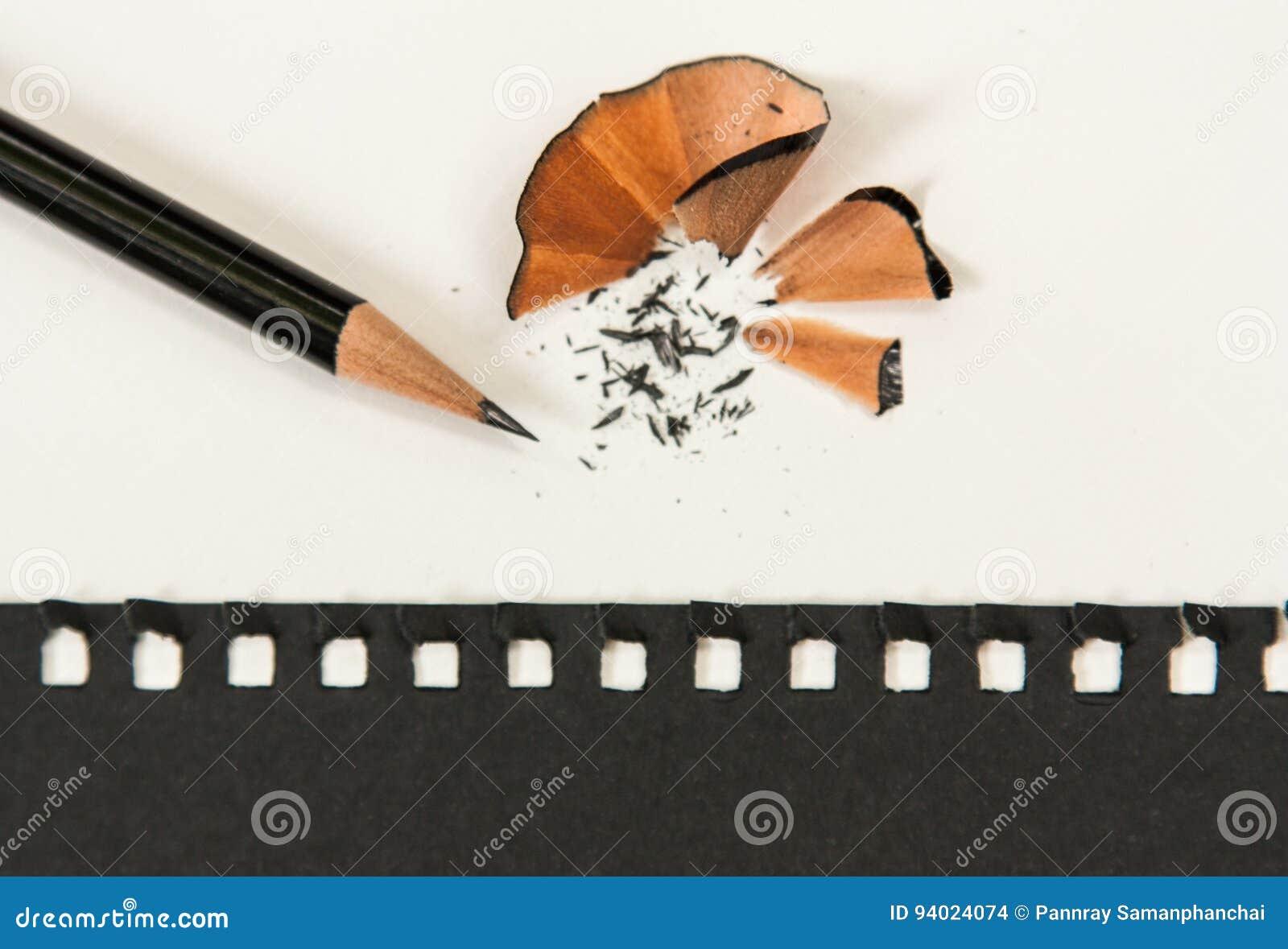 Заточите карандаш на белом столе С черной бумагой