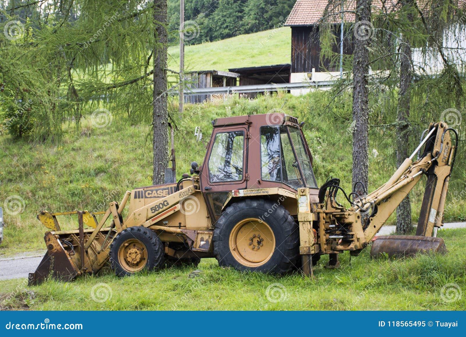 Затяжелитель экскаватора или машинное оборудование backhoe во время earthmoving работают на внешнем