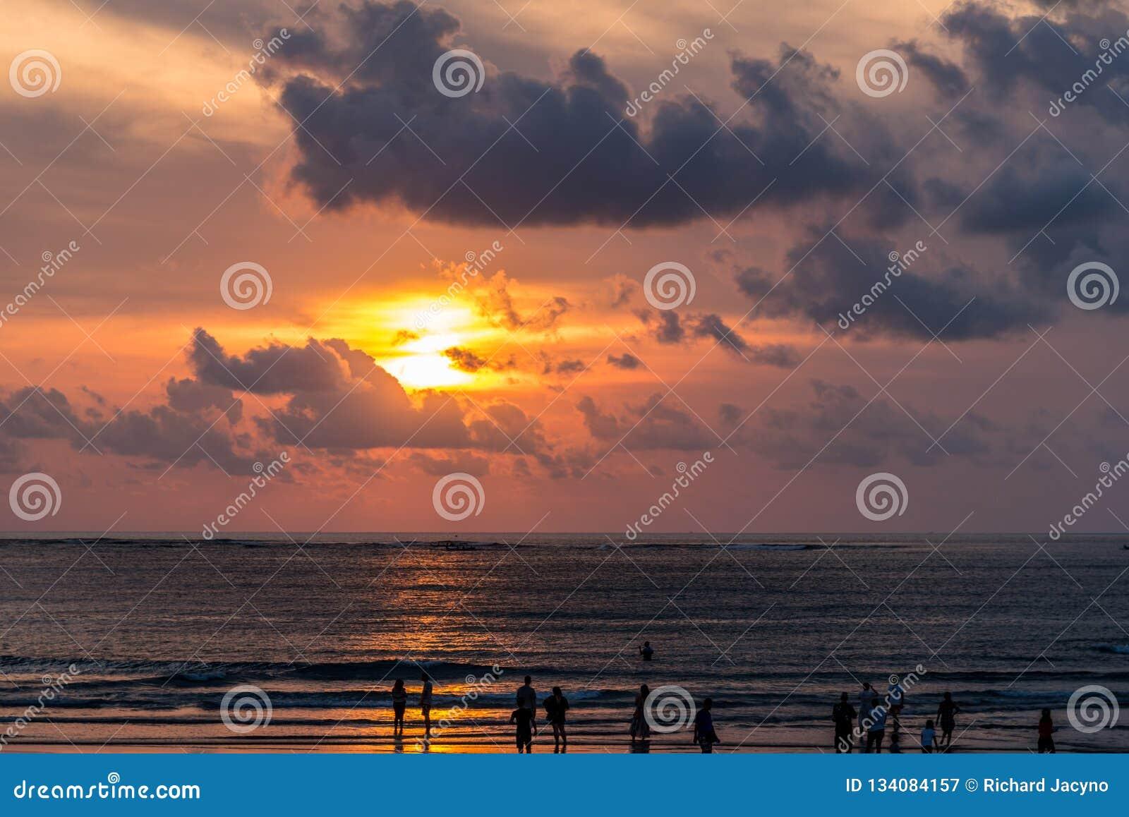Заход солнца Бали с людьми на пляже