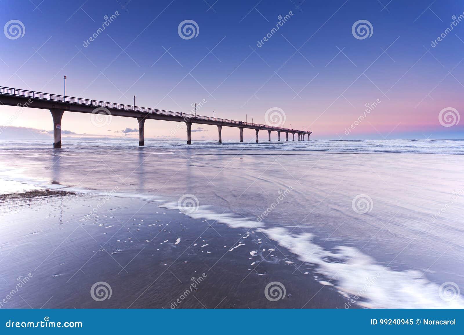 Заход солнца в новом пляже Крайстчёрче Новой Зеландии Брайтона
