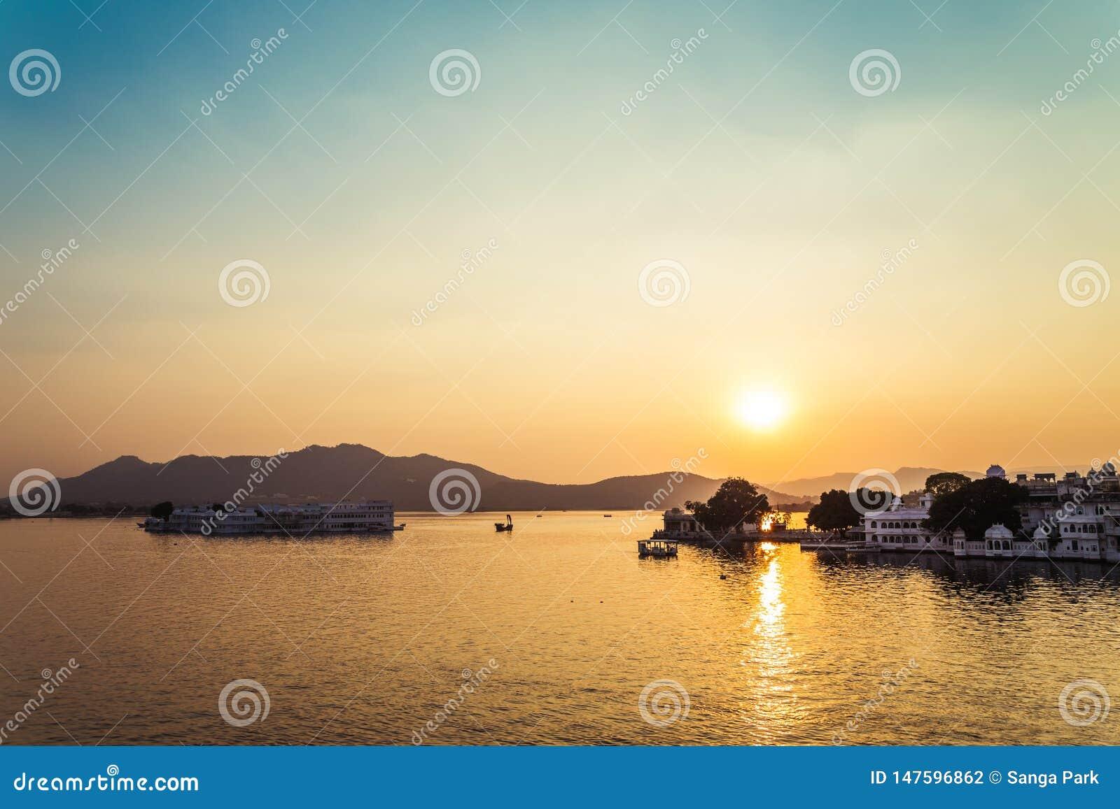 Заход солнца дворца озера Pichola и озера Taj в Udaipur, Индии