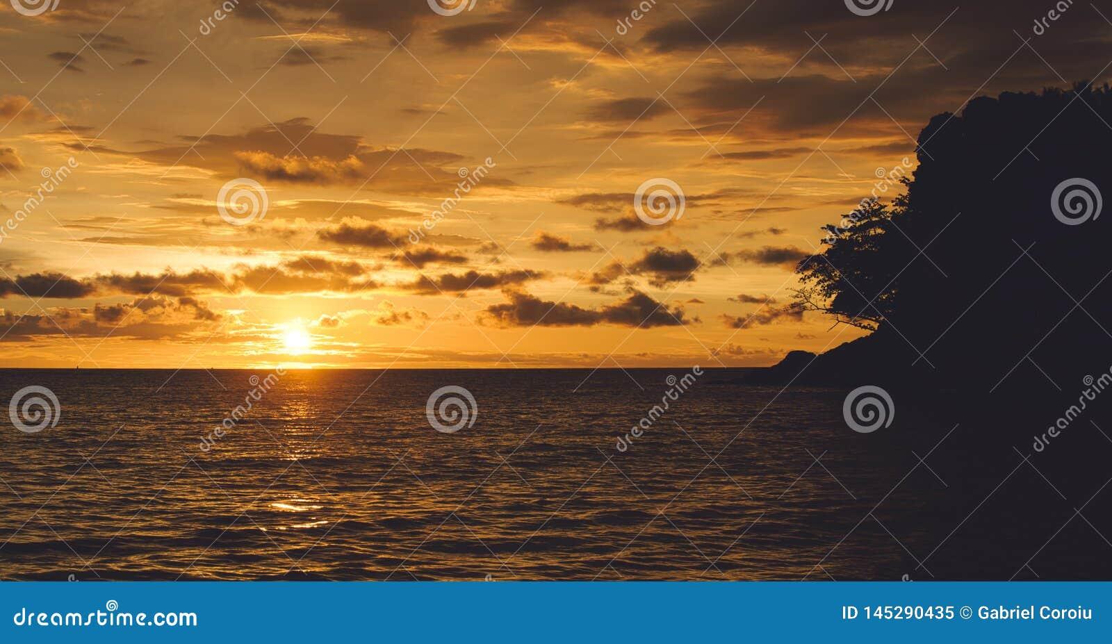 Заход солнца драматически на острове