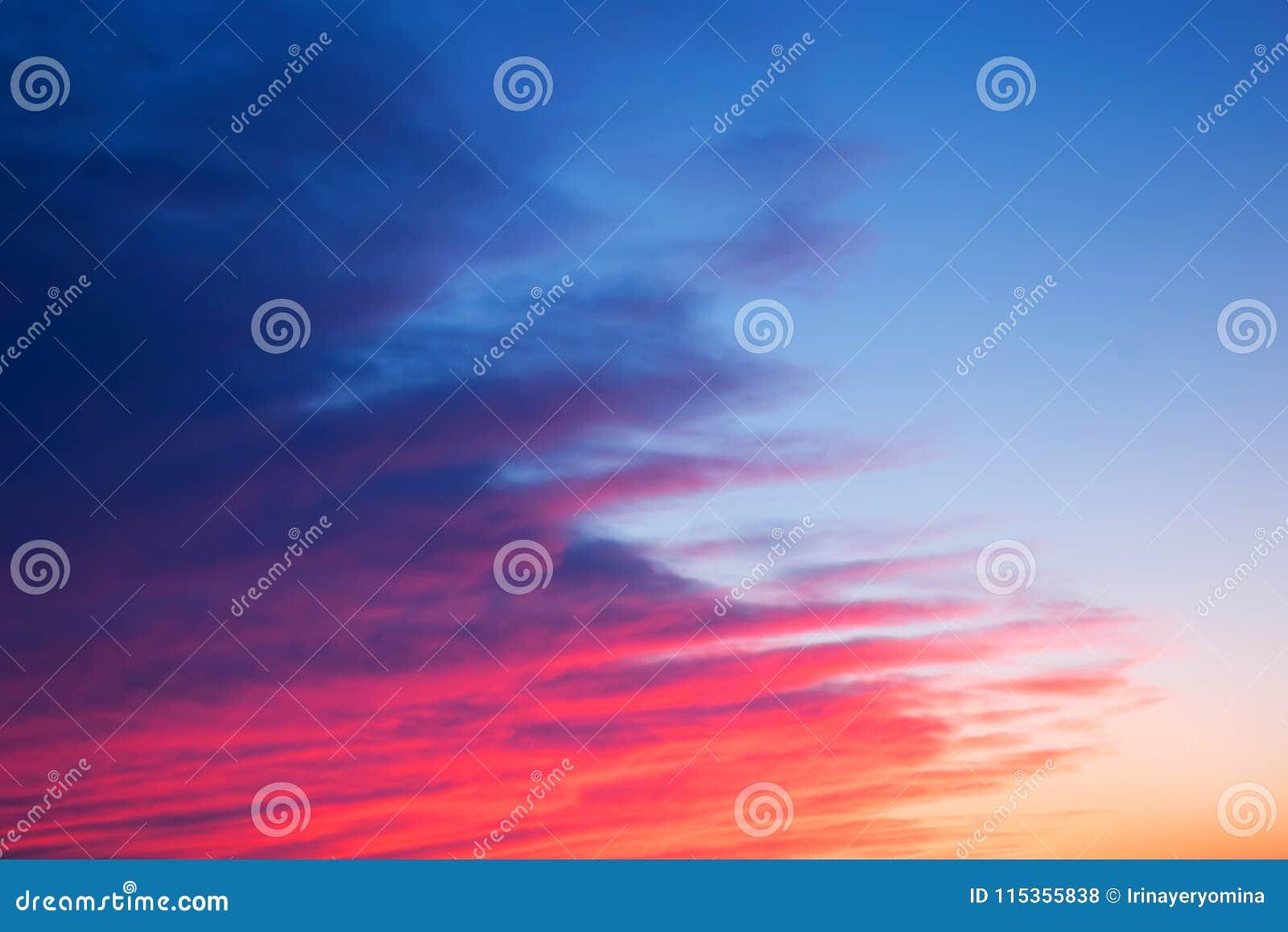 Заход солнца красного цвета, розовых и голубых яркий с красивыми раскосными облаками
