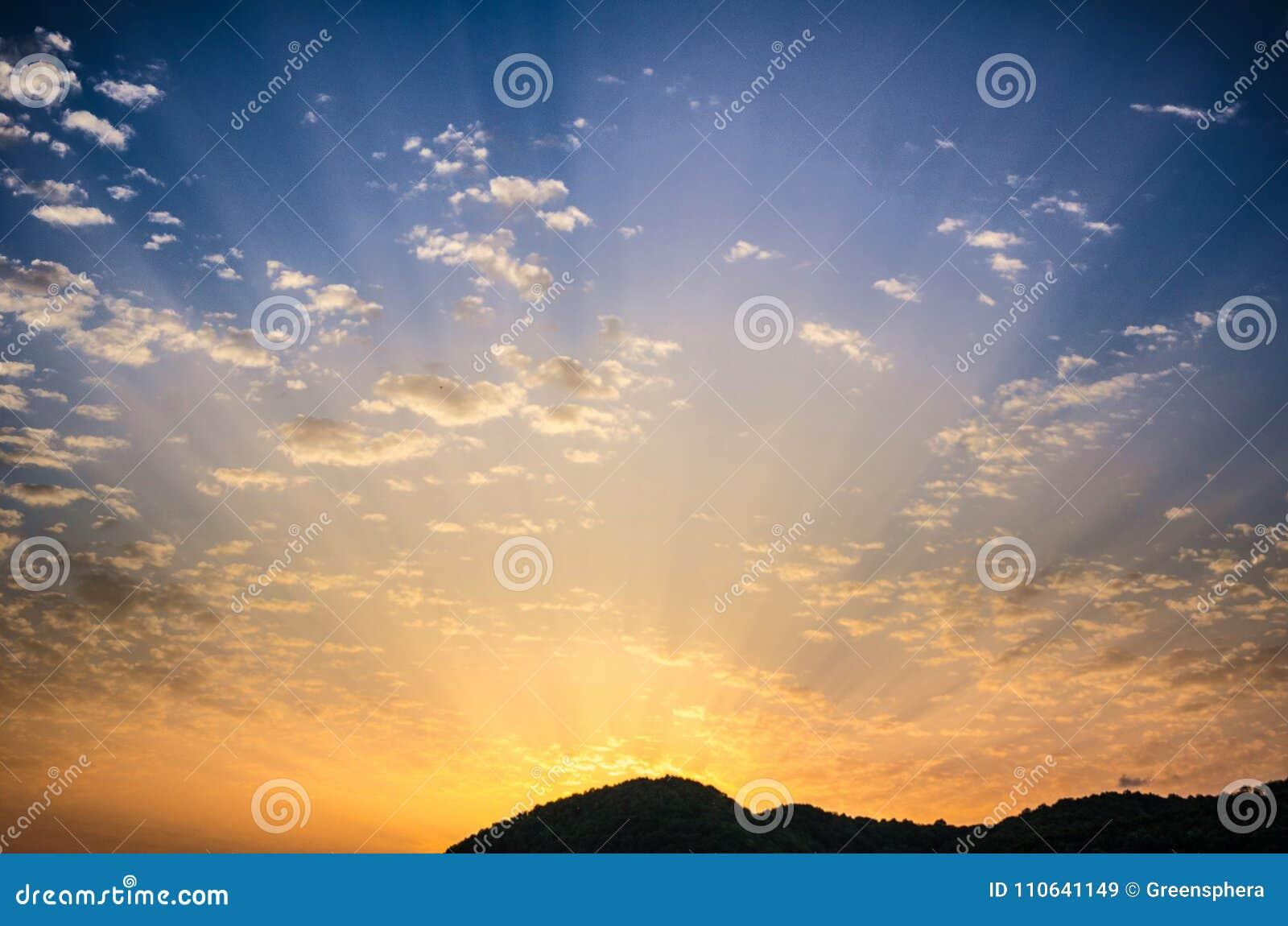 Заход солнца летнего дня красивый с золотым пасмурным красочным небом и изумительным излучающим солнцем излучает приходить от за