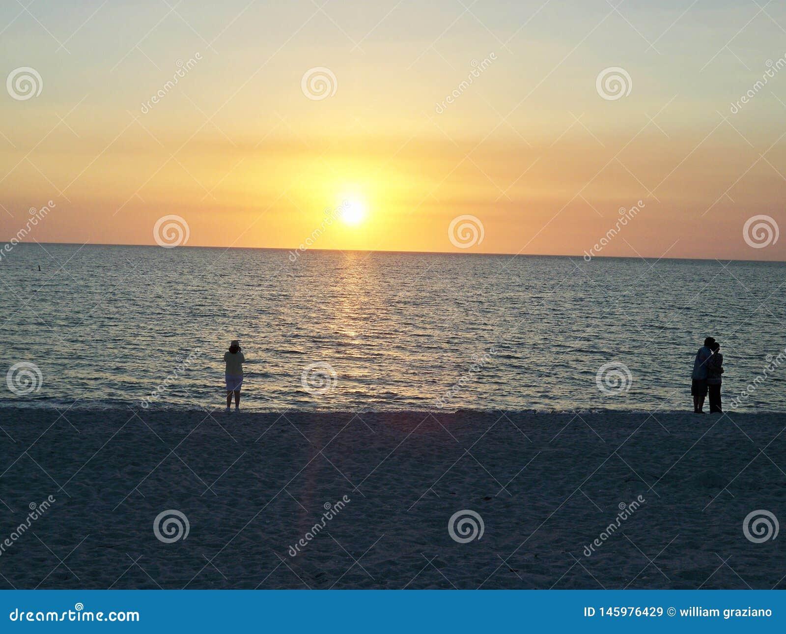 Заход солнца людей наблюдая на пляже
