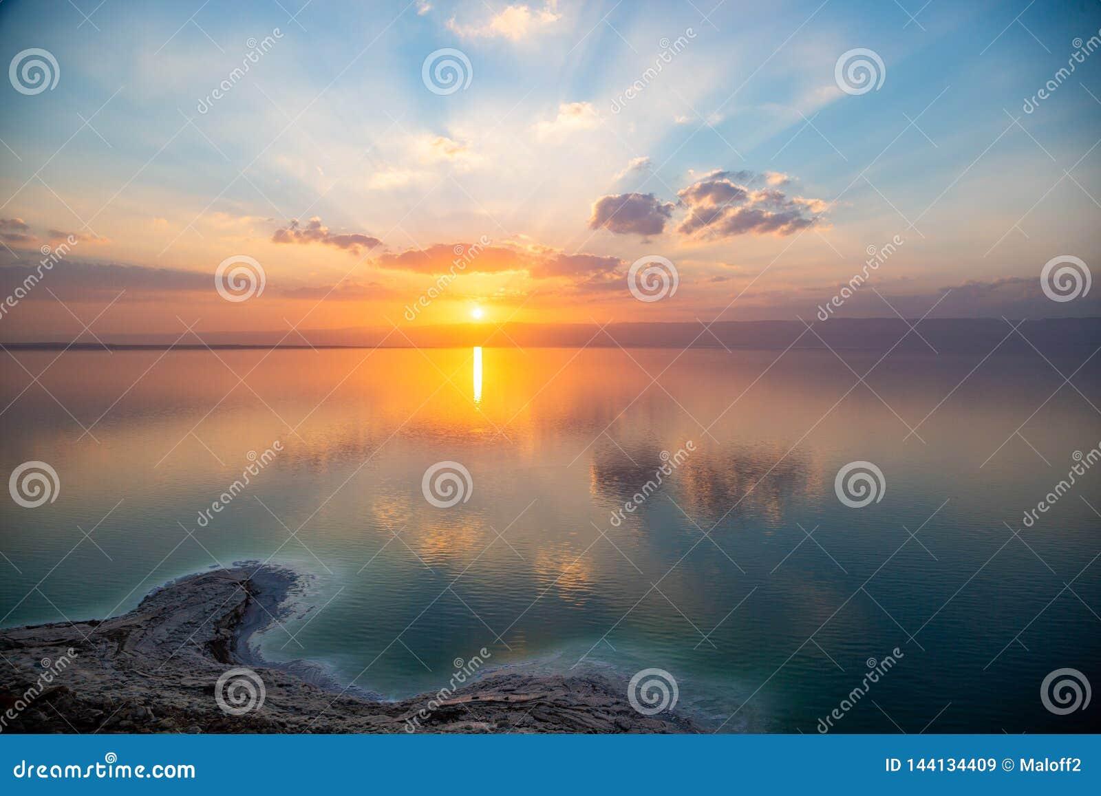 Заход солнца над мертвым морем, взгляд от Джордан к Израилю и горы Иудея Отражение солнца, небес и облаков Соленый пляж, соль