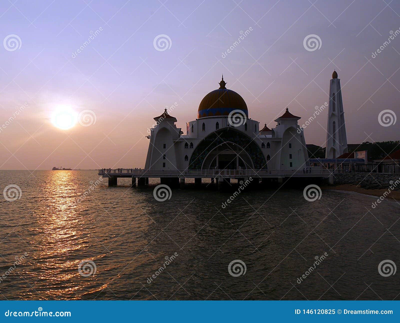 Заход солнца на плавая мечети Melakka Малайзии
