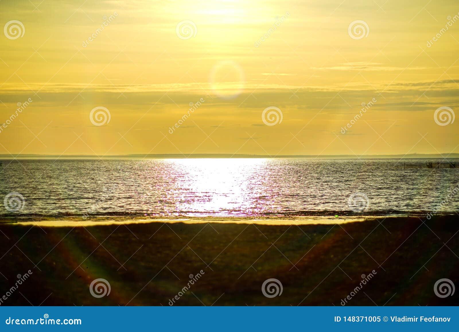 Заход солнца океана, моря на предпосылке солнца идя за горизонтом пляж и чудесное