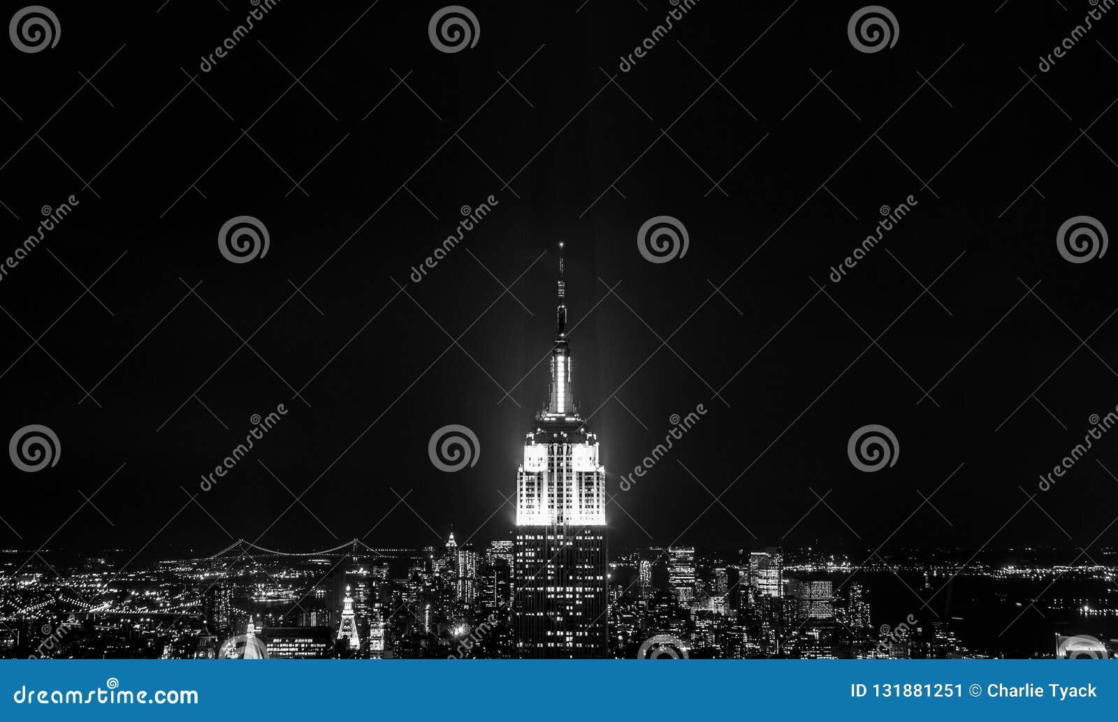 Заход солнца от вершины утеса - башенка Эмпайр-стейт-билдинг ярко освещенная в центре рамки - в черно-белом