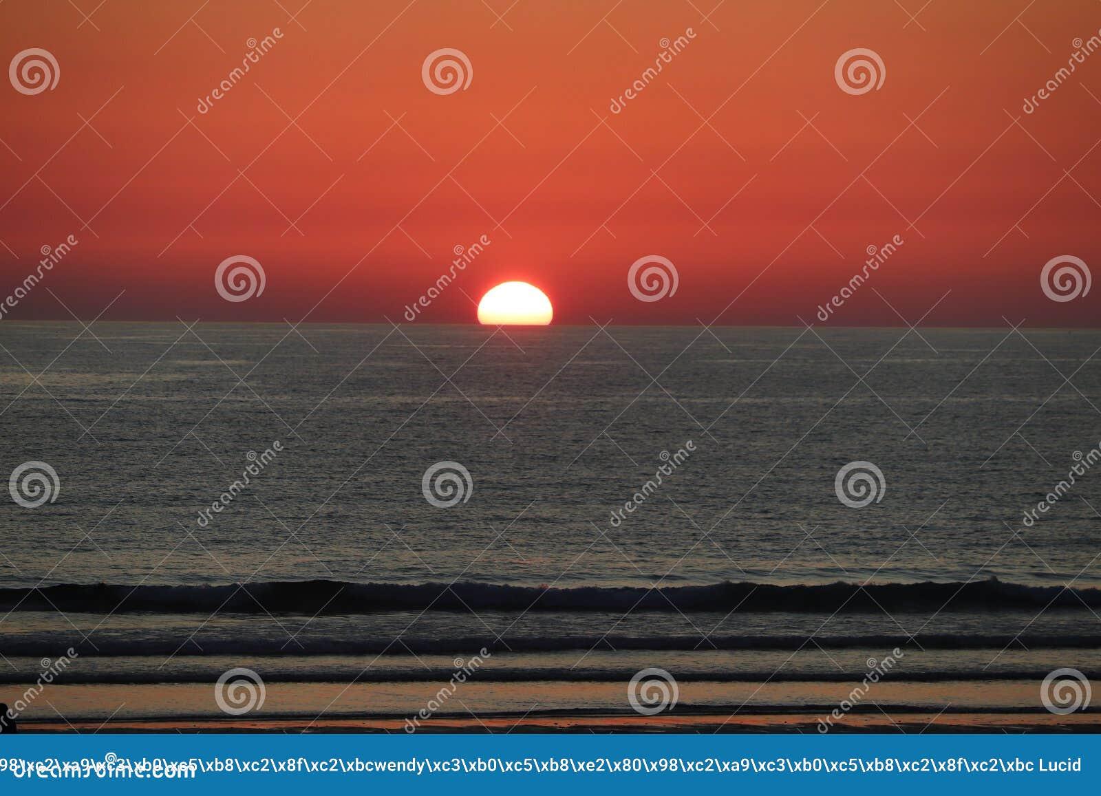 Заход солнца пляжа Newquay Корнуолла fistral, сногсшибательное зарево света