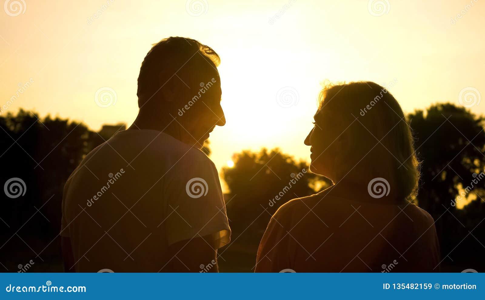 Заход солнца старшего силуэта пар наблюдая совместно, романтичная дата в сельской местности