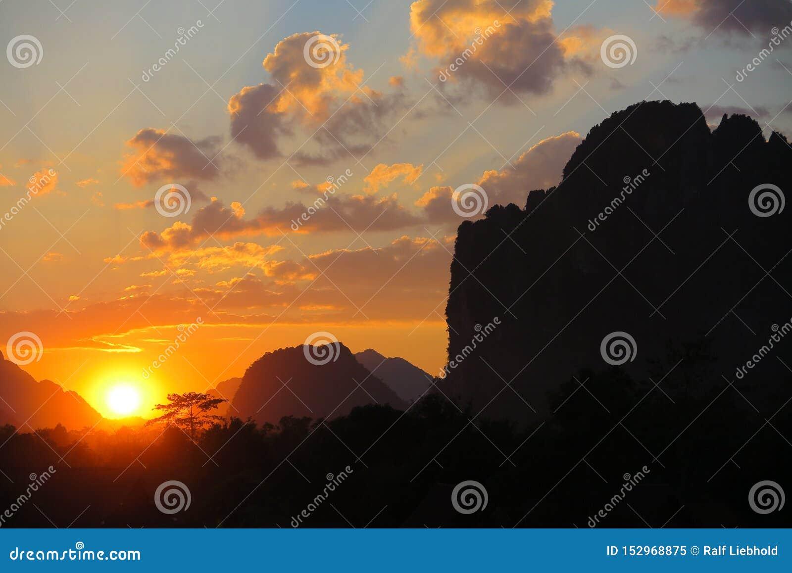 Заход солнца с желтыми золотыми цветами и черным силуэтом горной цепи известняка karst - Vang Vieng, Лаоса
