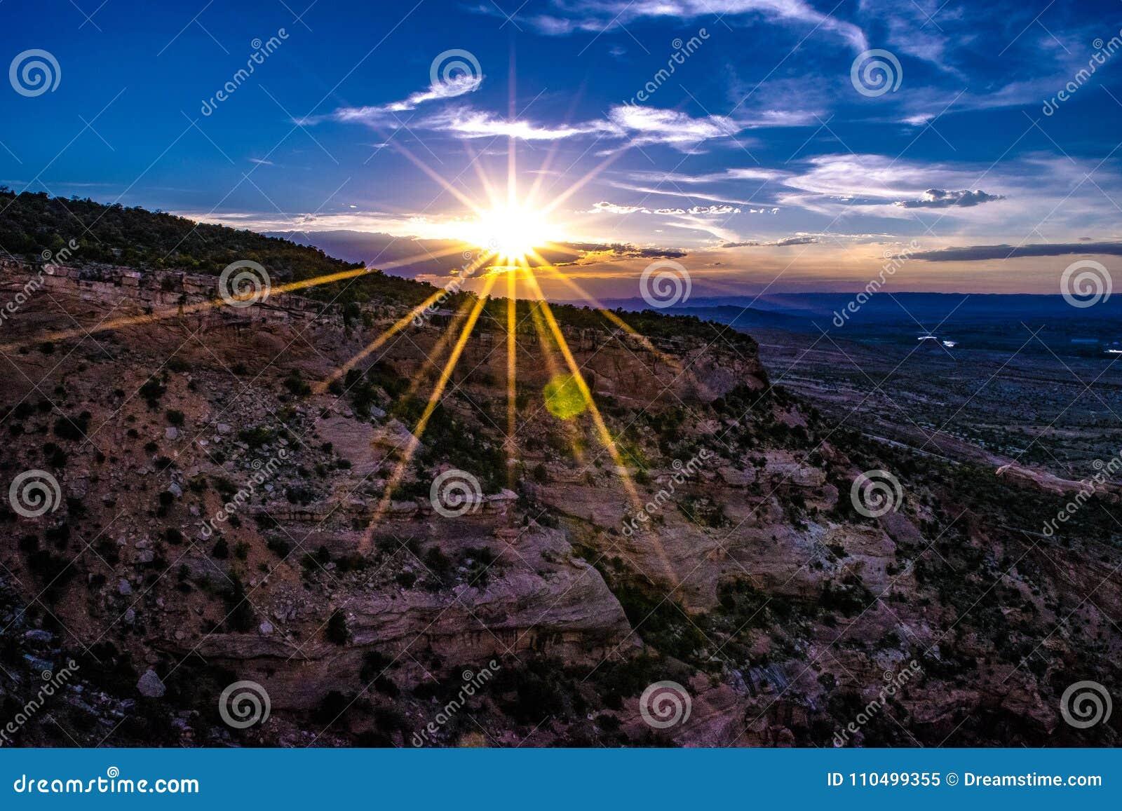 Заход солнца через ущелье каньона на памятниках в Grand Junction, Колорадо