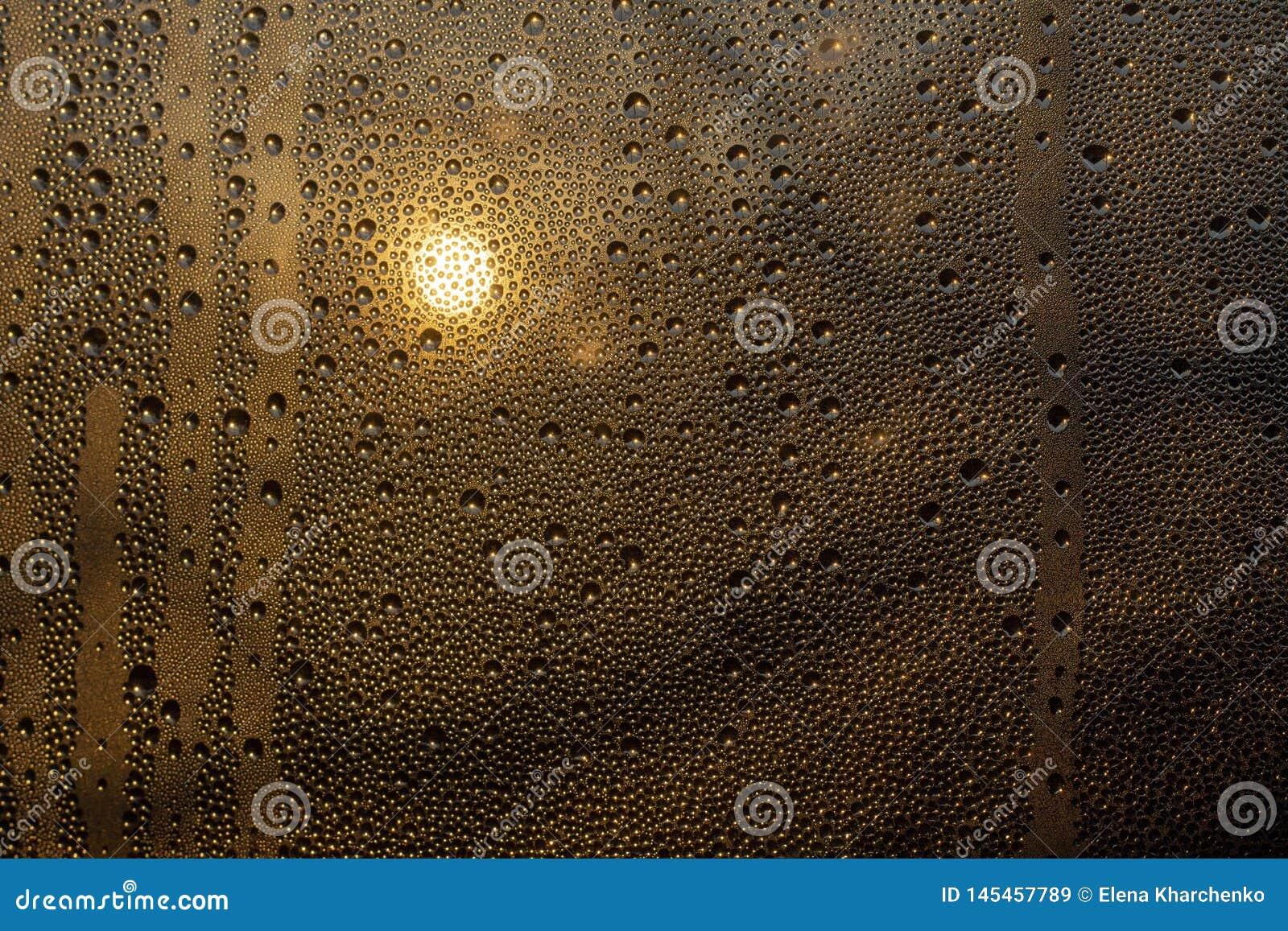 Заход солнца через misted стекло с падениями и потеками