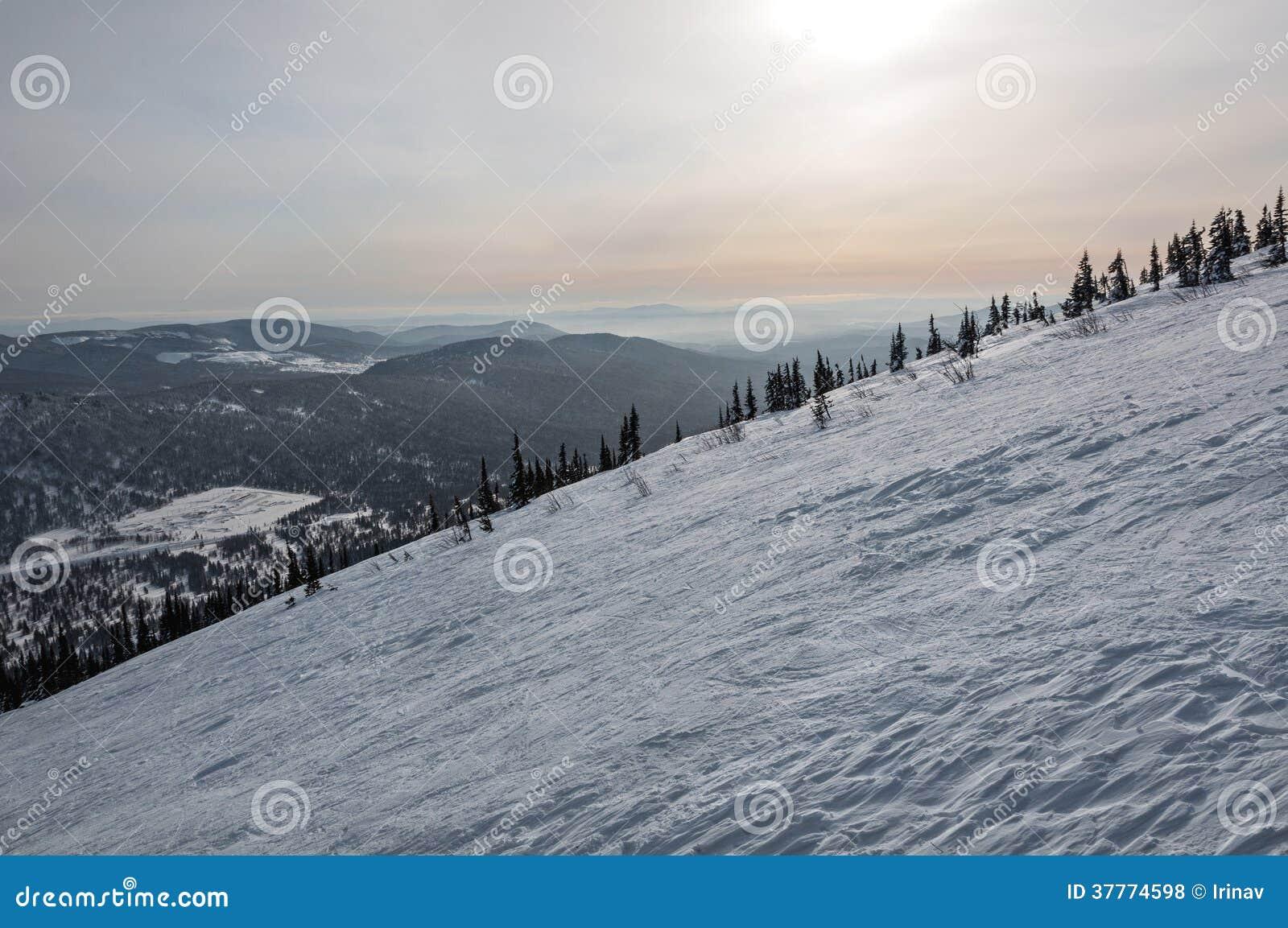 Заход солнца зимы снега наклона горы