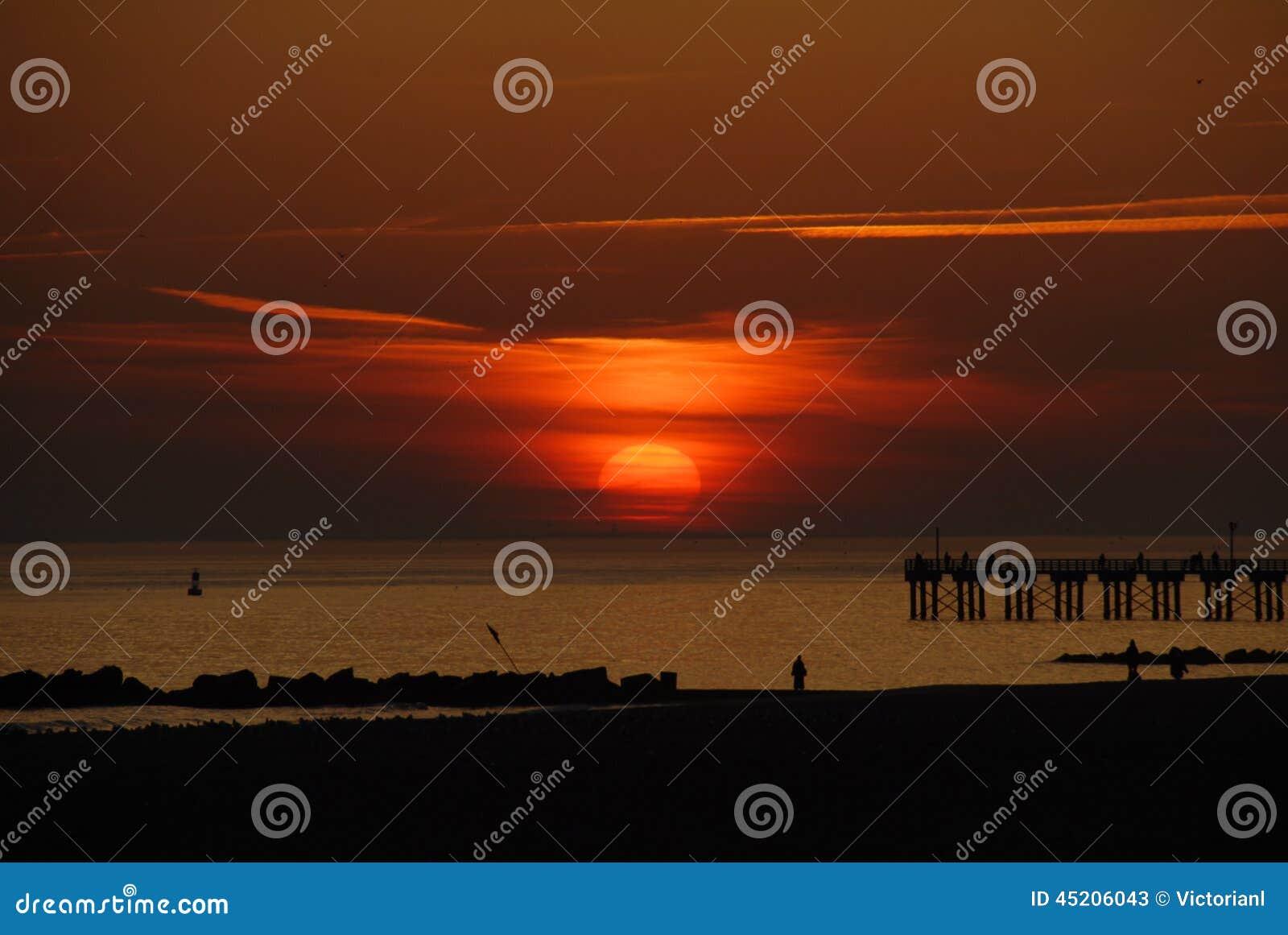 Заход солнца от пляжа Брайтона, Нью-Йорка