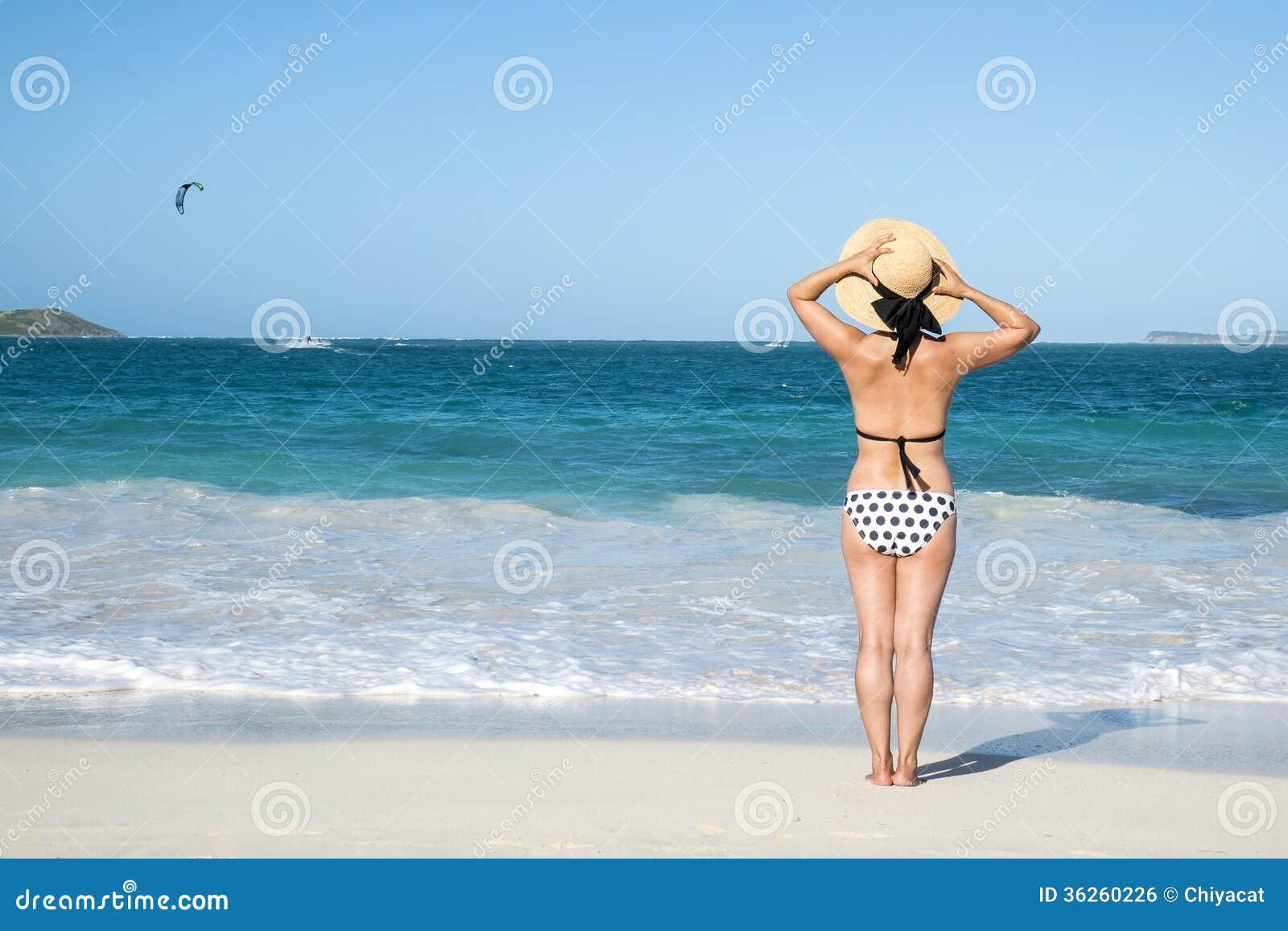 Задний взгляд женщины в бикини точки польки стоя на пляже 1