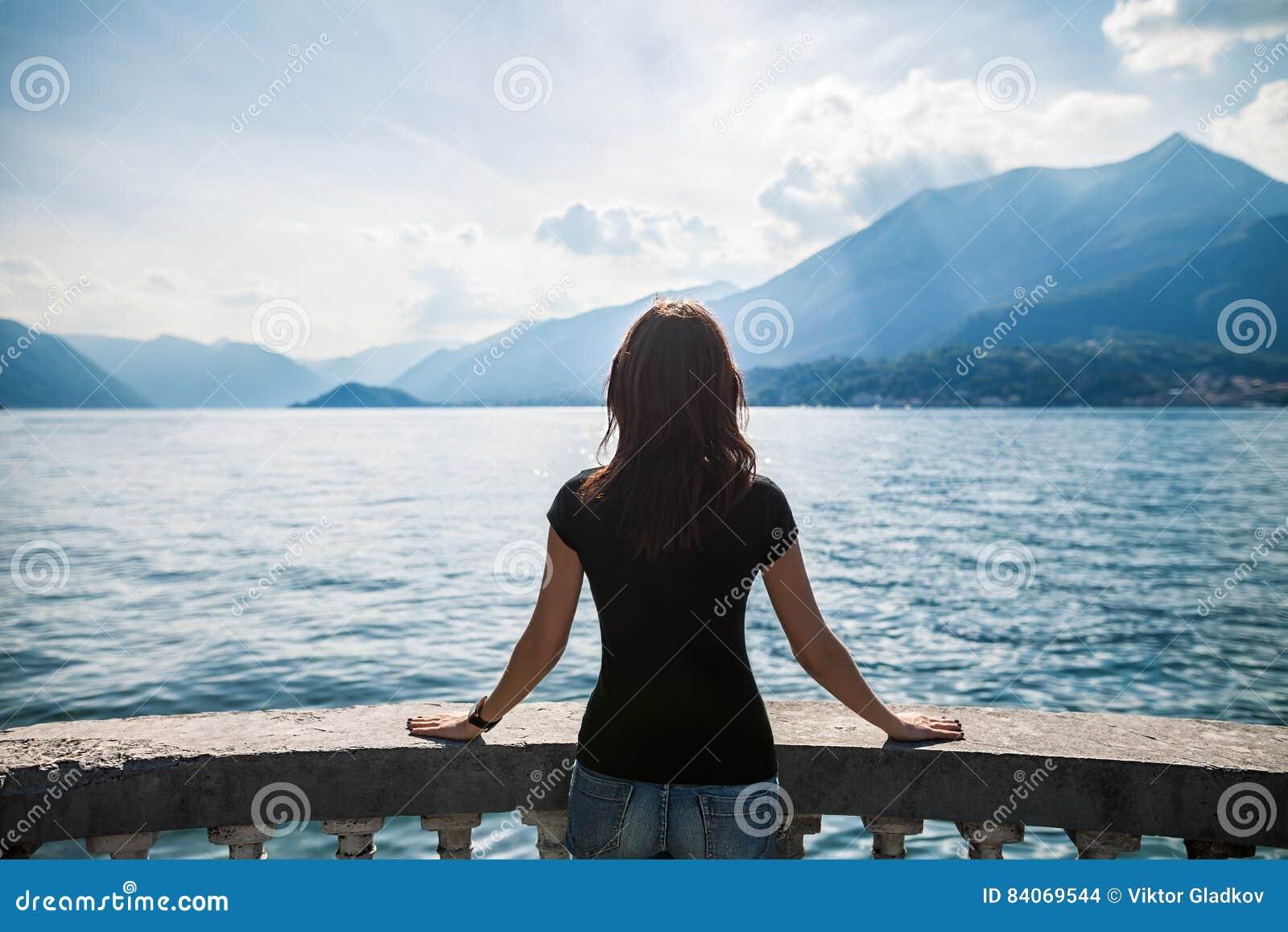 Задний взгляд молодой женщины ослабляя на террасе на озере Como, Италии