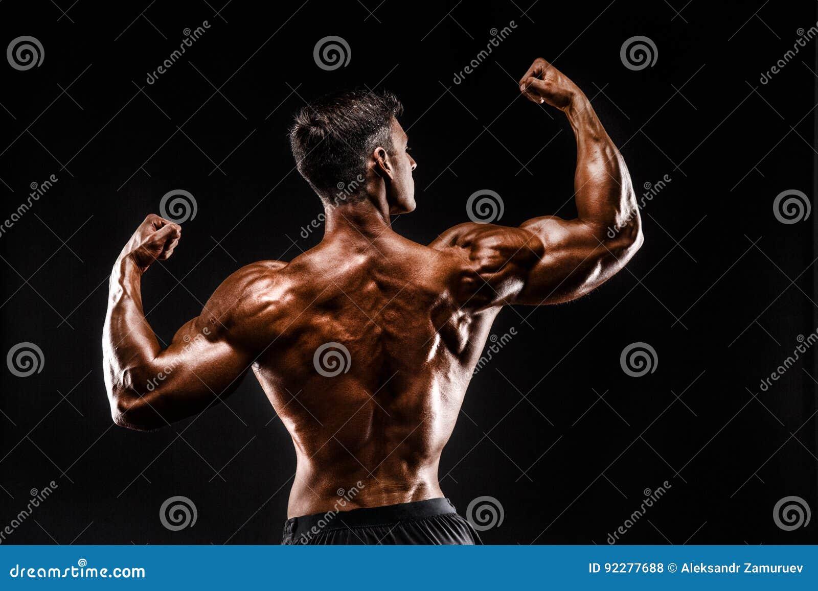 Задний взгляд непознаваемого человека, сильных мышц представляя с оружиями вверх