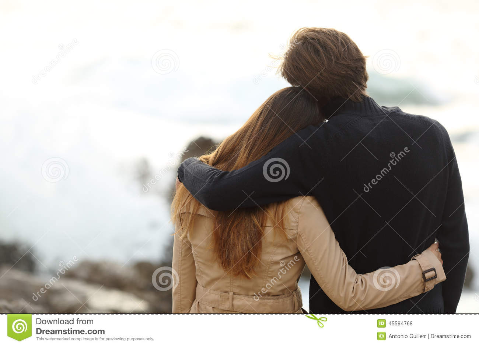 Задний взгляд пары прижимаясь в зиме