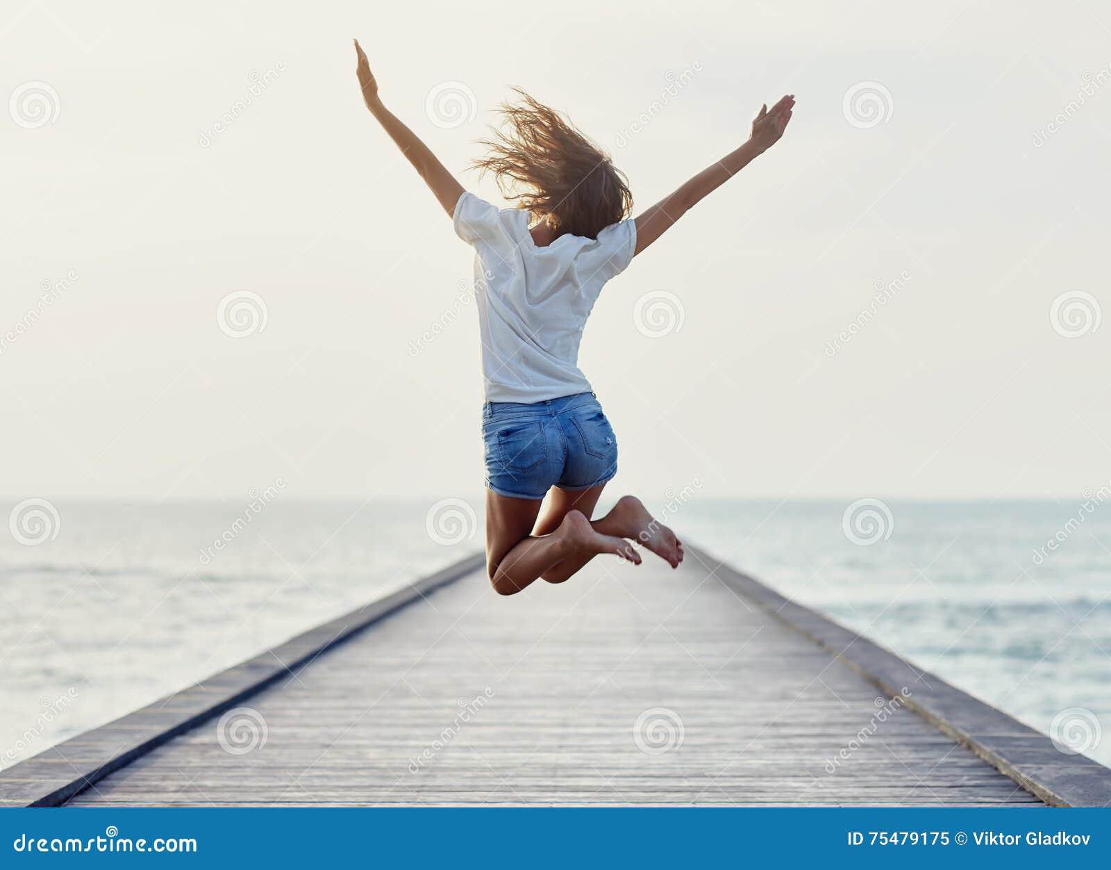 Задний взгляд скача девушки на пристани