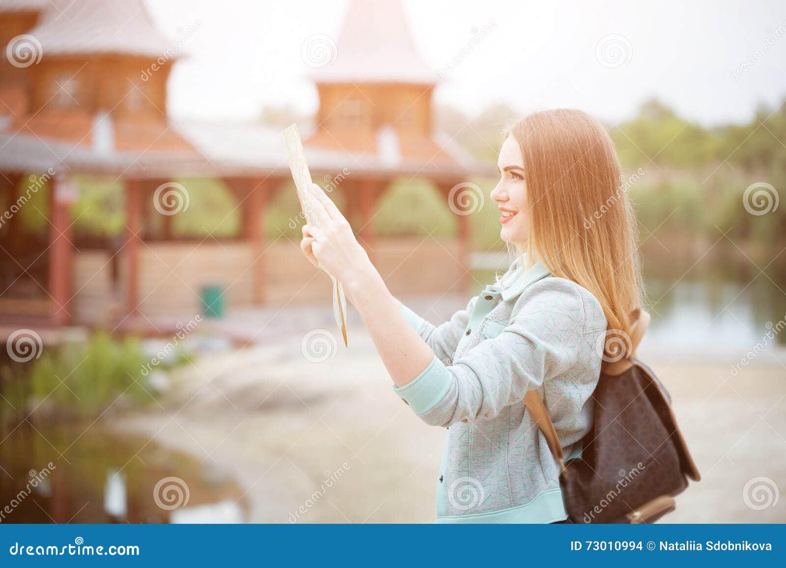 Задняя сторона девушки путешественника ища правильное направление на карте, оранжевом свете захода солнца, путешествуя вдоль Евро